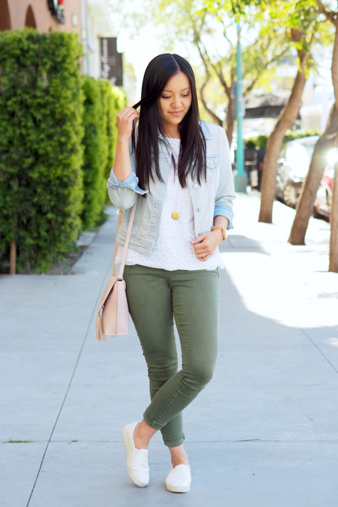 Olive Jeans Outfit: white lace top + denim jacket + olive skinny jeans + white slip-on sneakers + blush crossbody bag + gold disc pendant necklace
