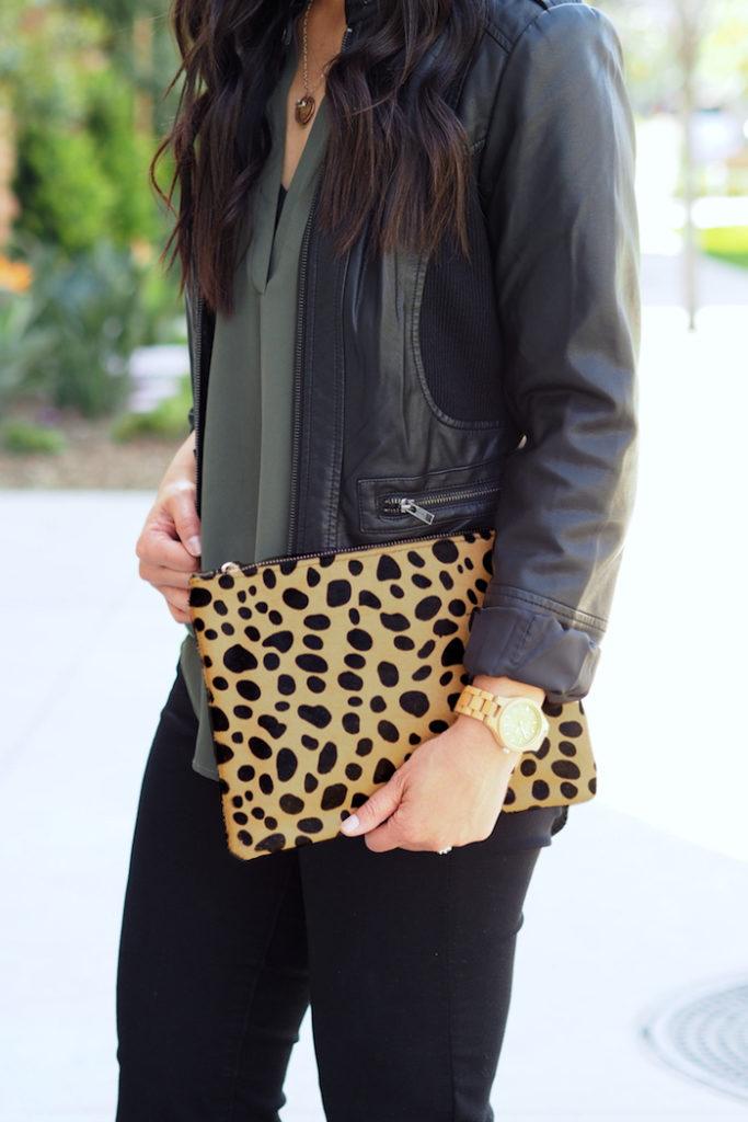 olive top + black moto jacket + leopard print clutch