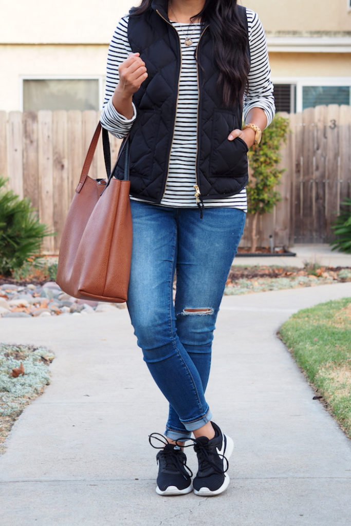 black vest + striped tee + distressed jeans + black sneakers