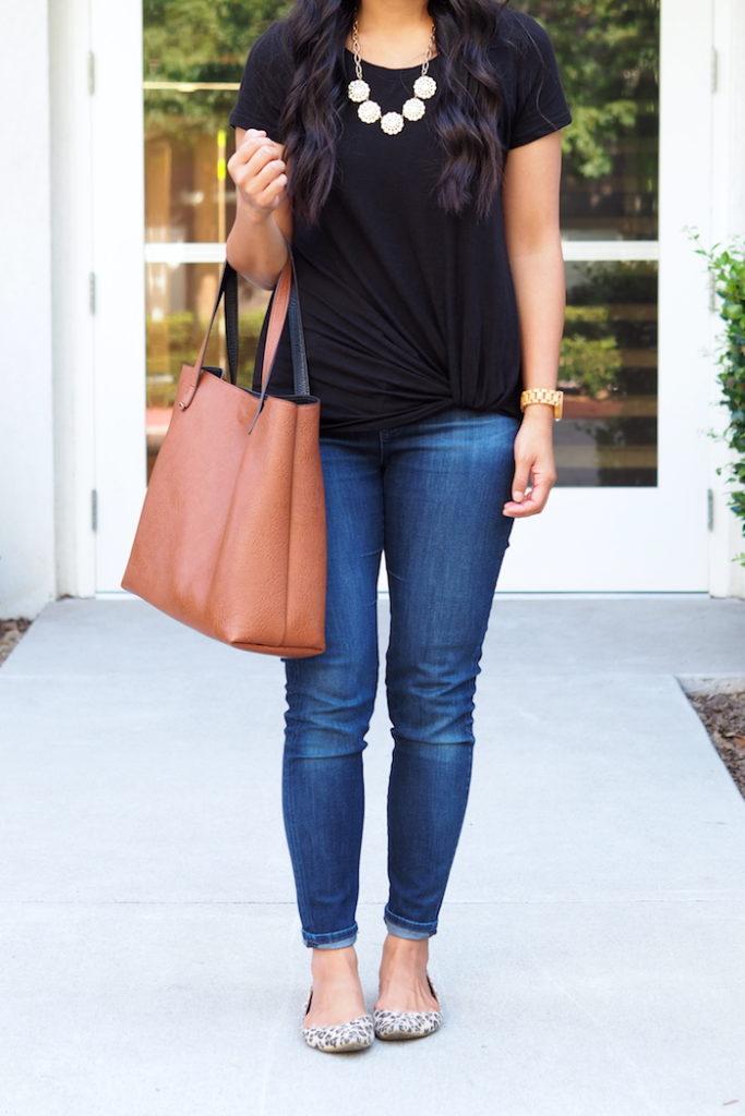 black twist tee + dark wash jeans + leopard flats + statement necklace + cognac tote