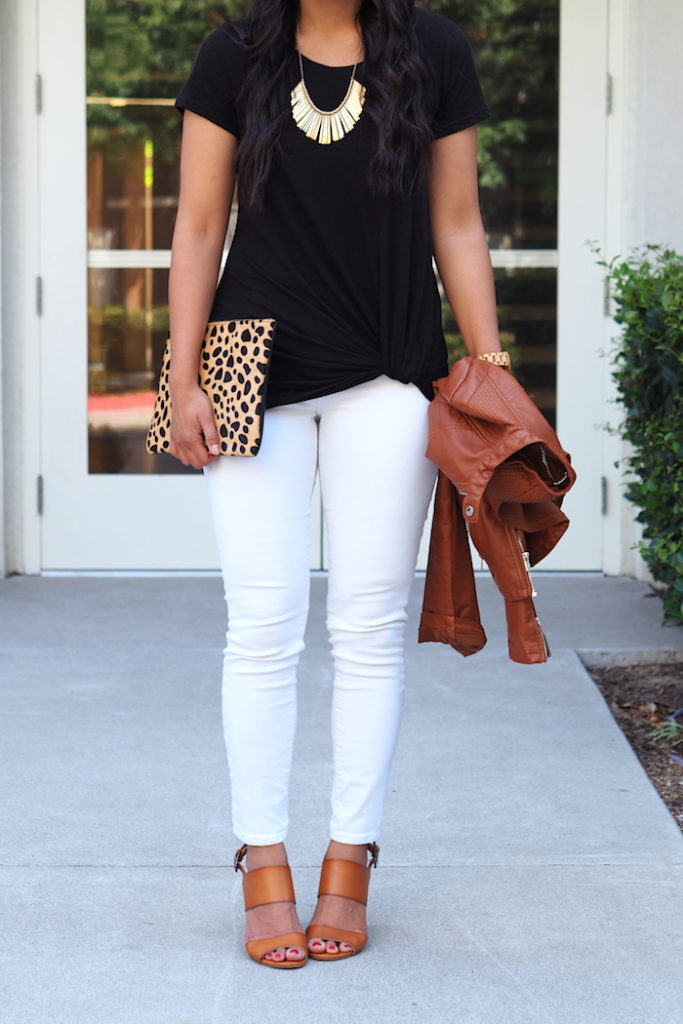 black twist tee + metallic statement necklace + leopard clutch + white jeans + cognac