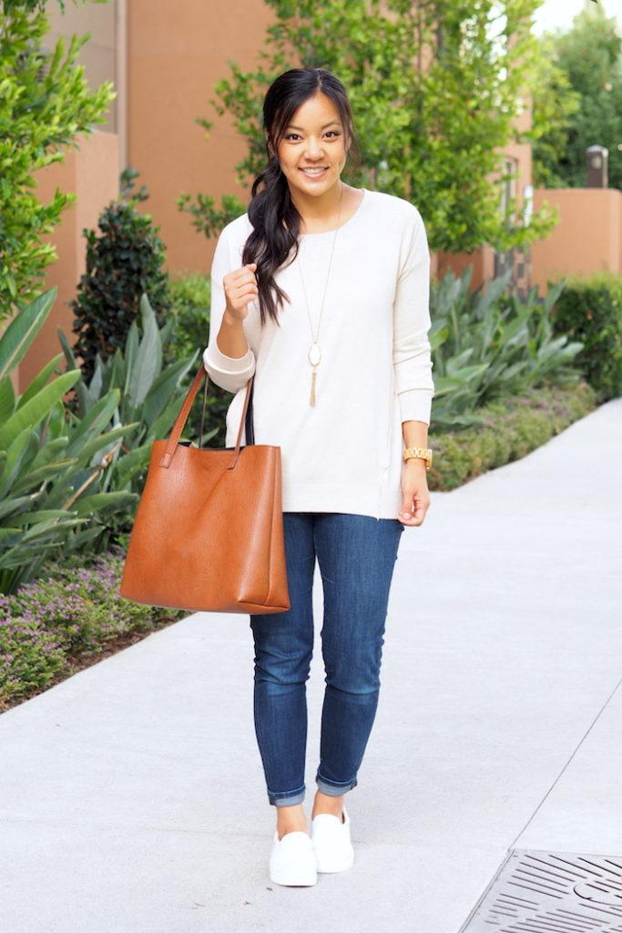 beige sweater + dark wash jeans + white sneakers