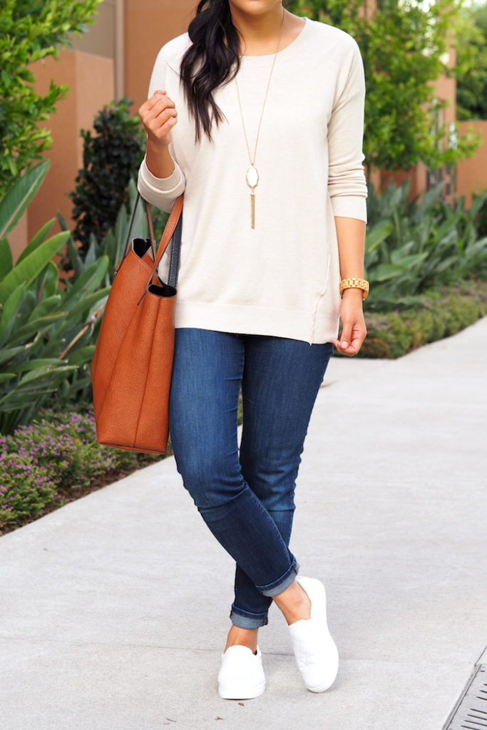 beige sweater + dark wash jeans + white sneakers + white tassel necklace
