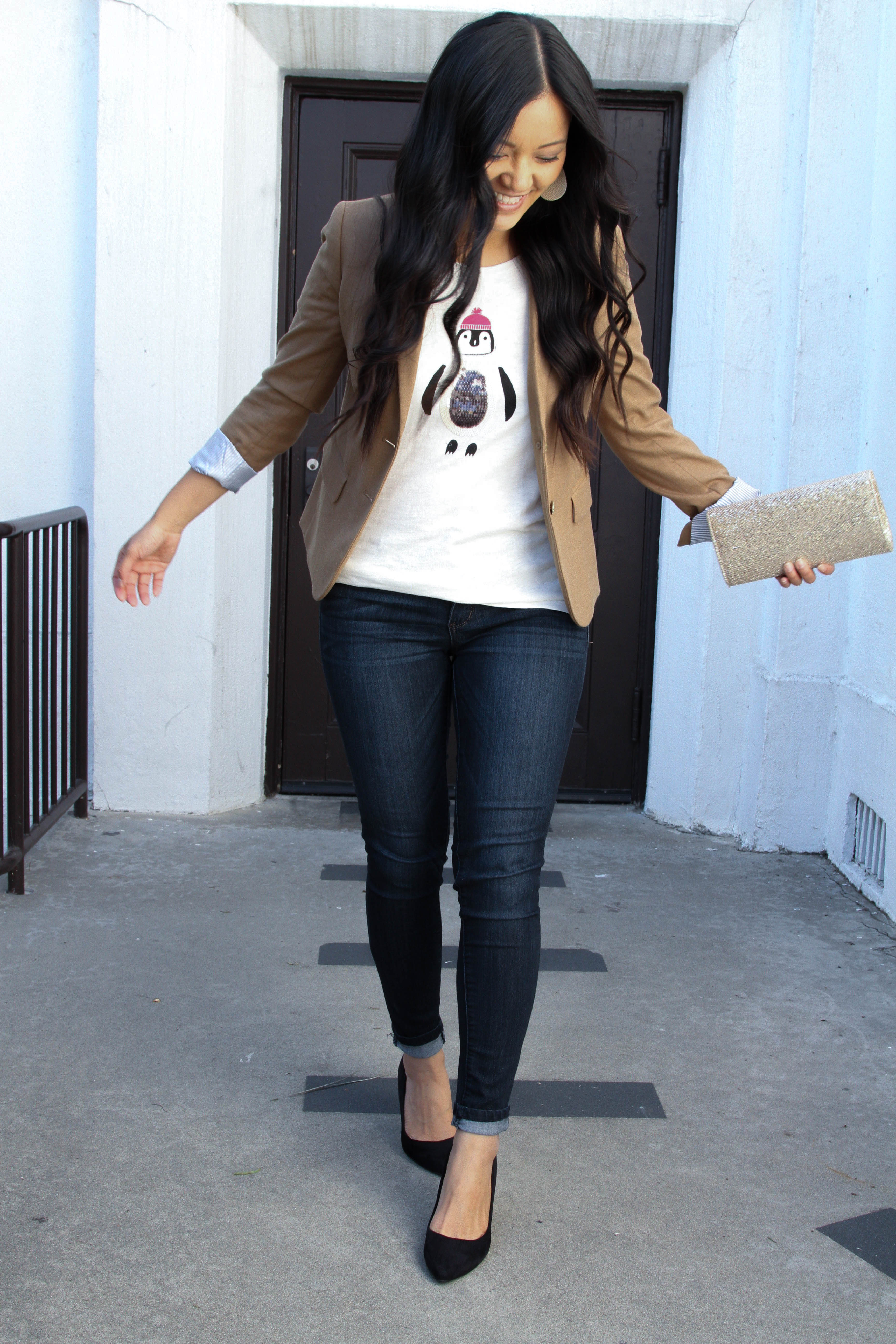 Skinnies + Black Pumps + holiday t-shirt + tan blazer + gold clutch