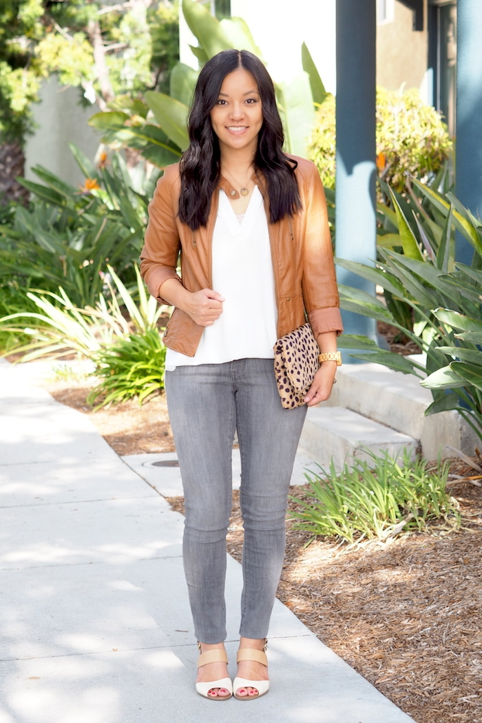 white blouse + grey jeans + tan moto jacket + leopard print clutch