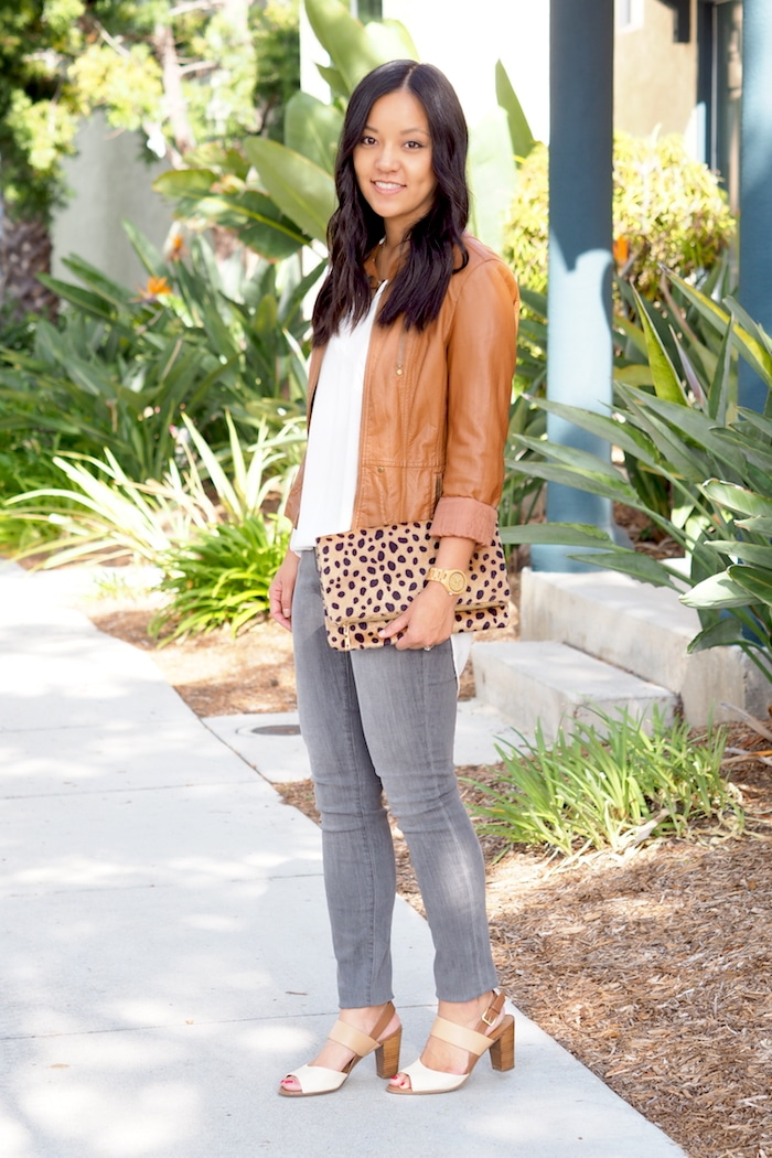 white top + cognac moto jacket + leopard print clutch + grey jeans