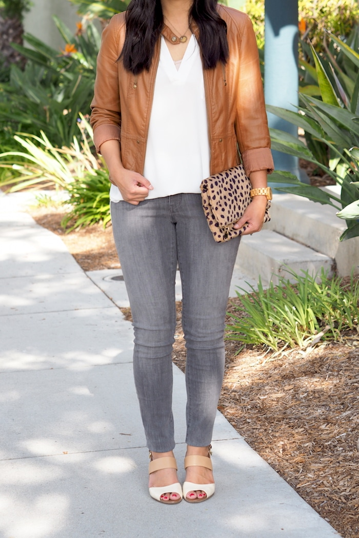 white top + grey jeans + cognac moto jacket + leopard clutch