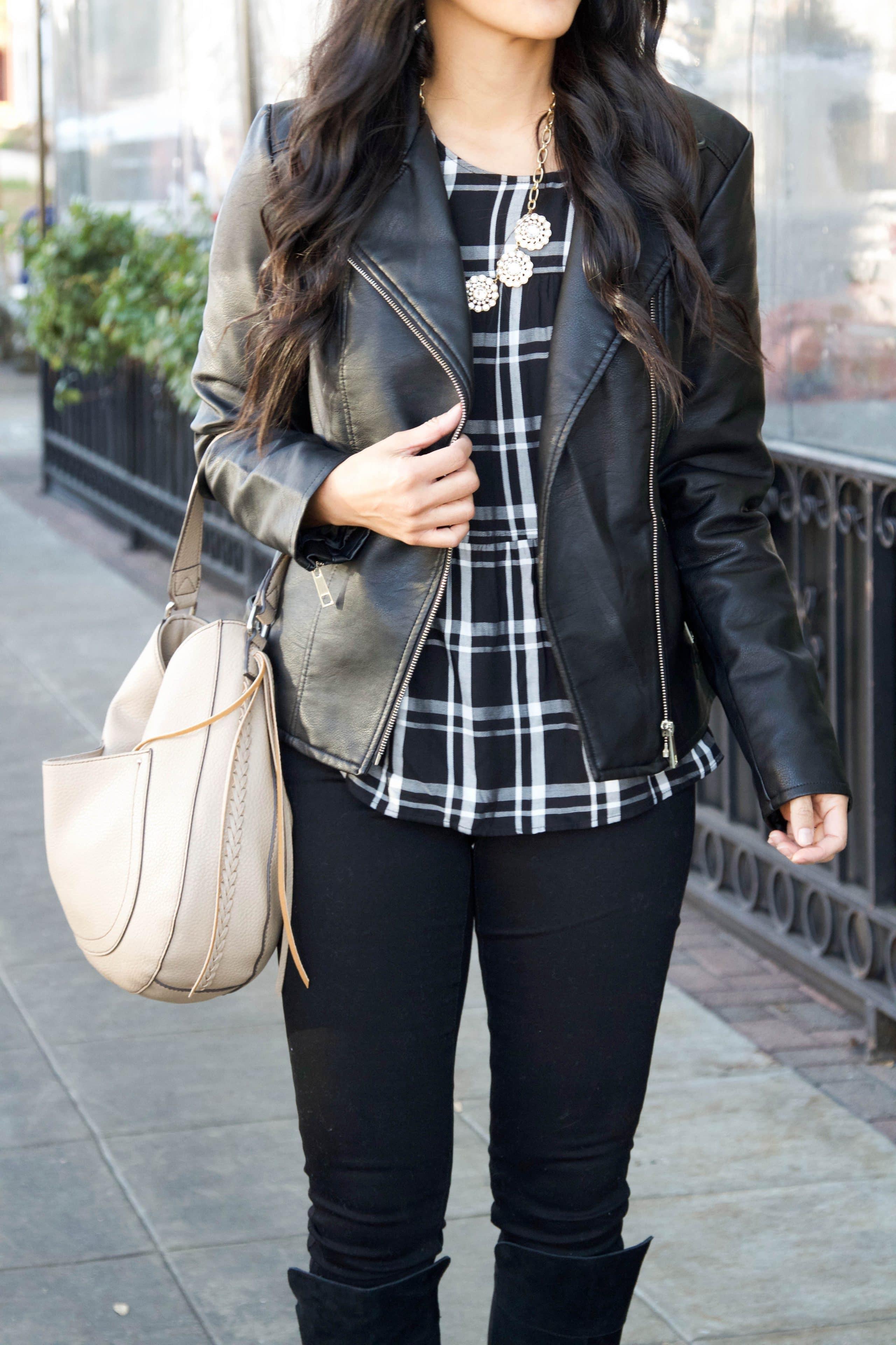 Black moto + black jeans + black tall boots + tan bag