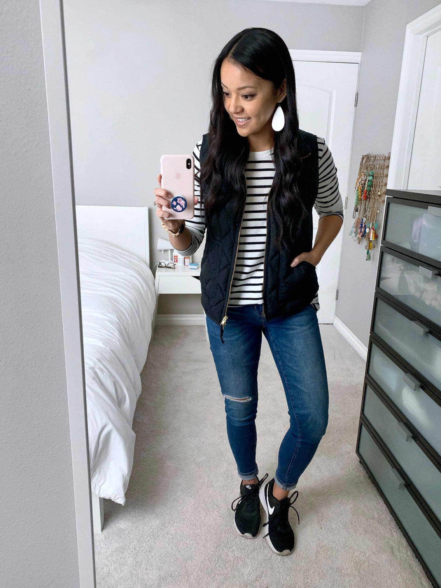 Black Vest + Striped Top + Distressed Jeans + Black Sneakers + White Earrings