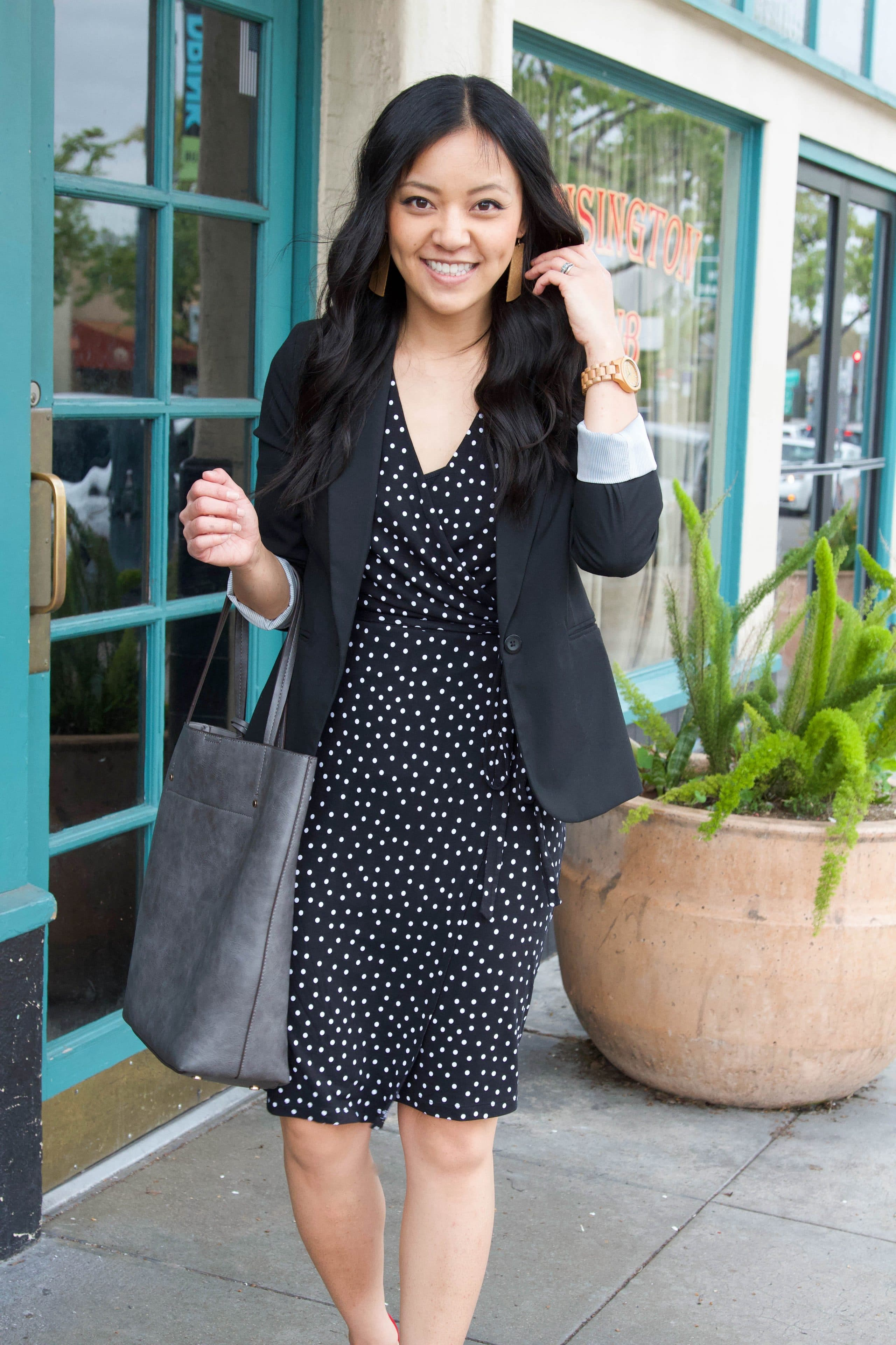 business casual outfit + wooden watch + polka dot black dress + black blazer + grey tote + brown earrings