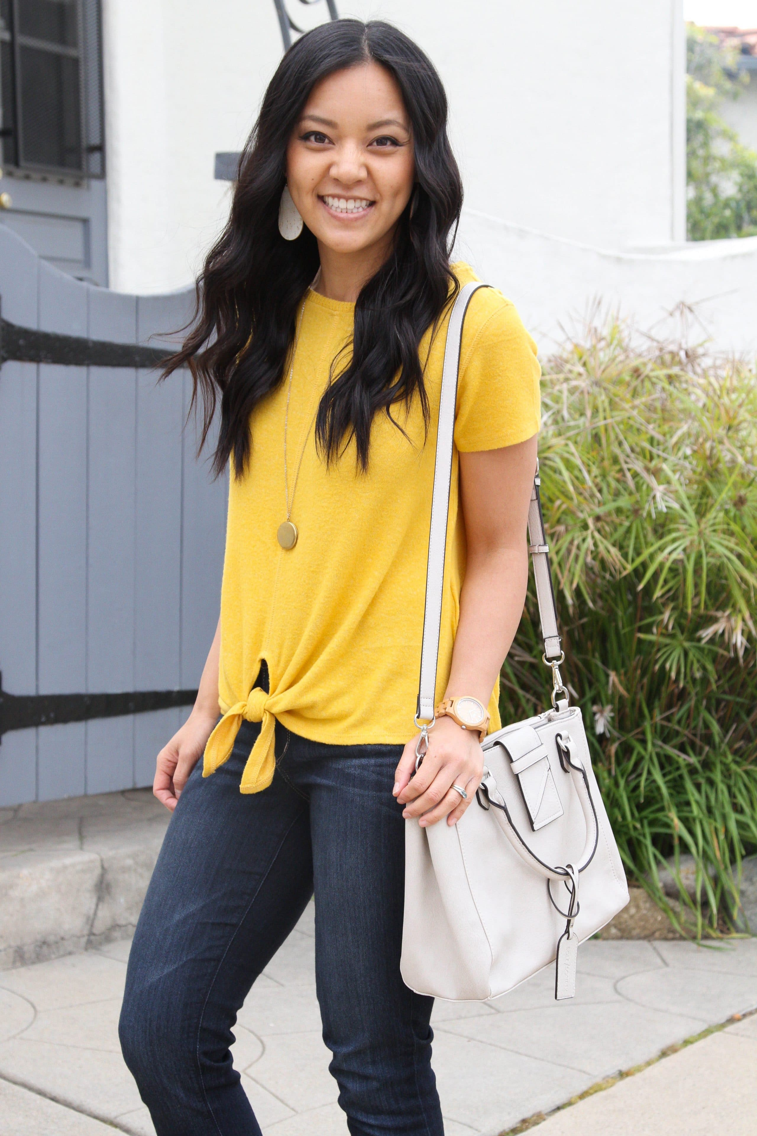 Yellow tie top + bootcut jeans + white bag + yellow wedges