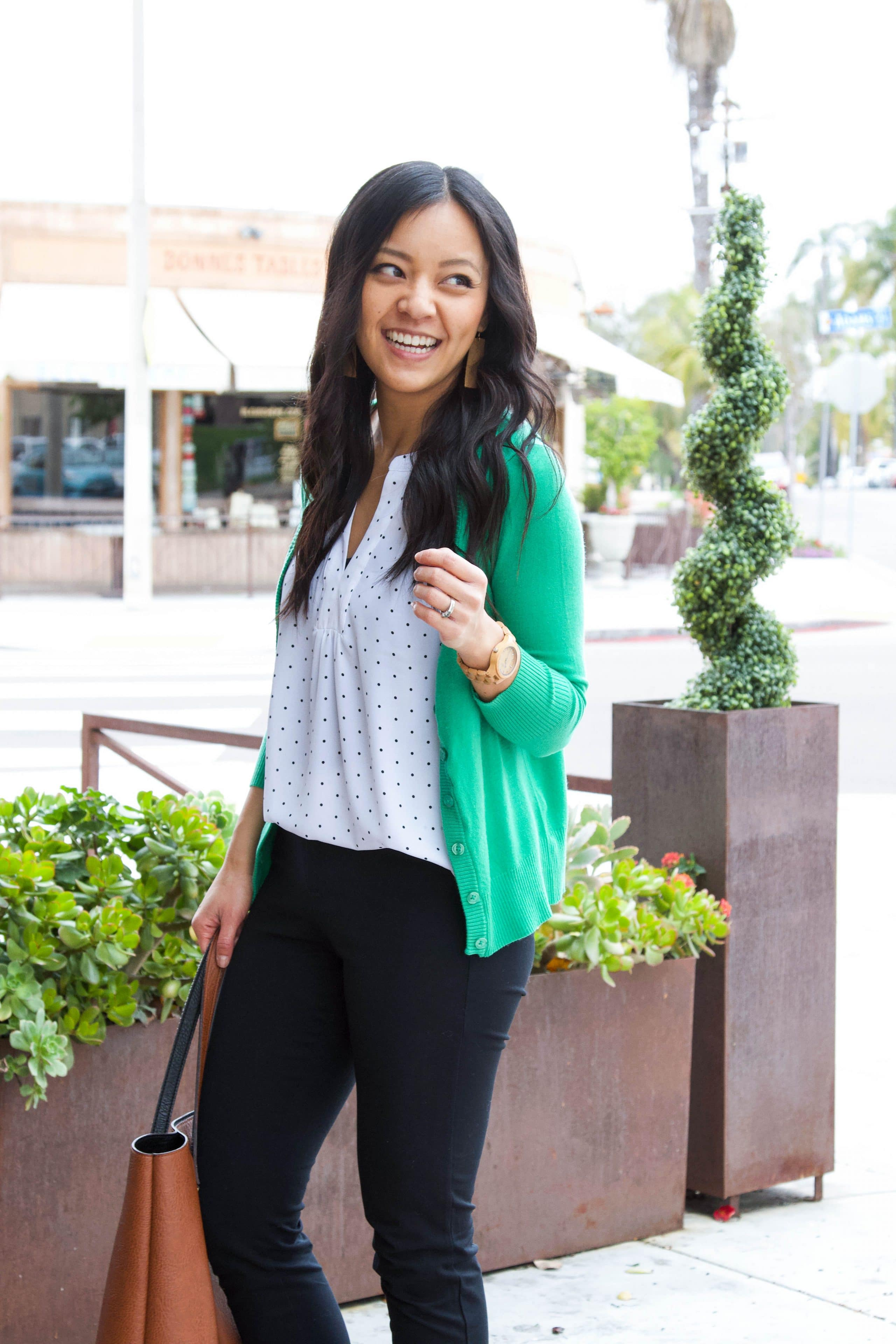 business casual outfit + black ankle pants + cognac tote + white polka dot shirt + green sweater