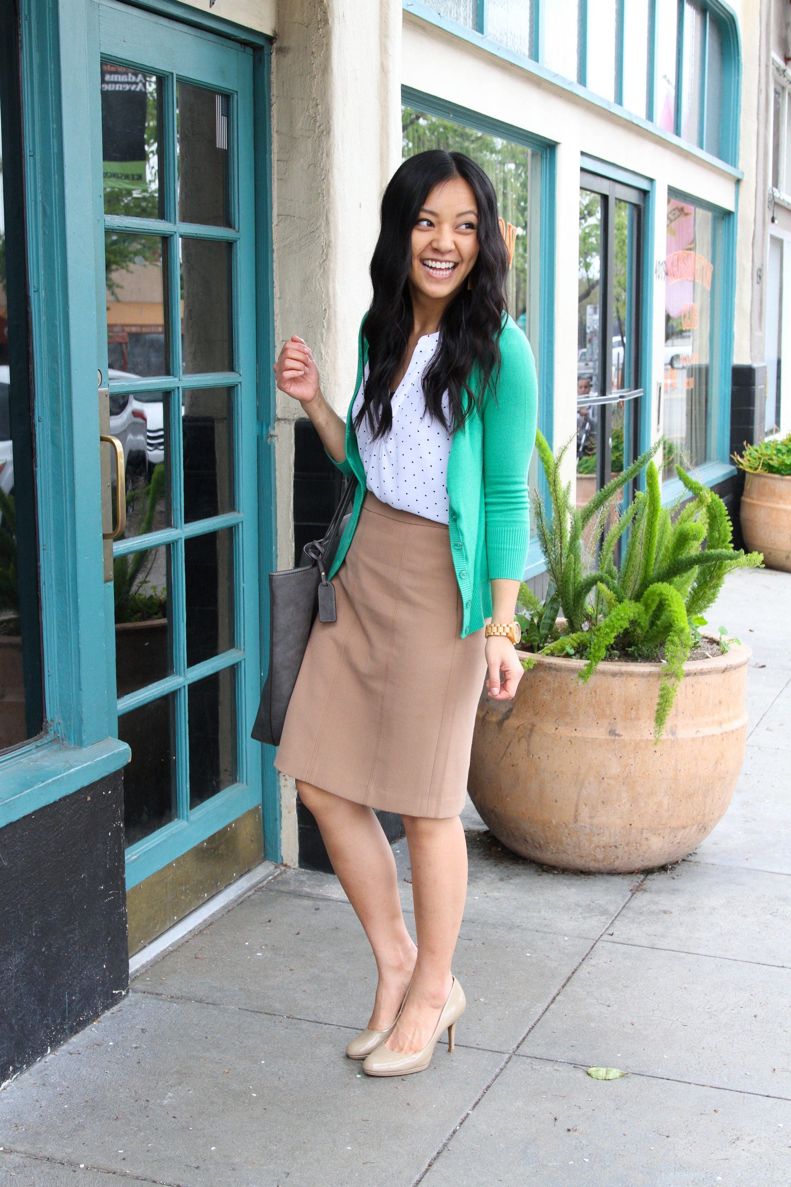 business casual outfit + green cardigan + white blouse + tan skirt + nude pumps