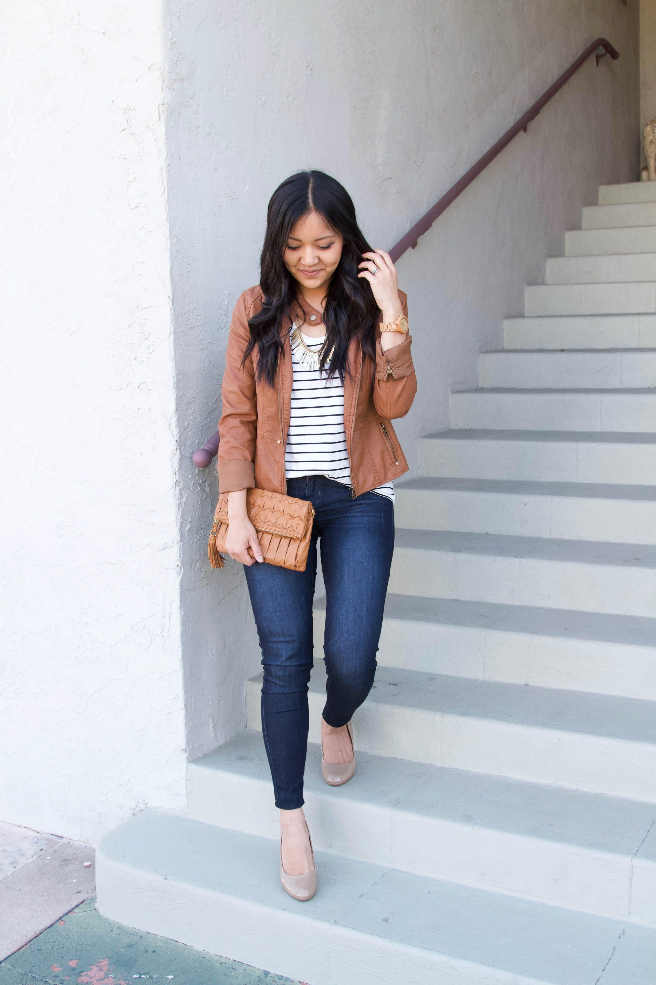 brown moto jacket + brown clutch + striped tee + skinny jeans