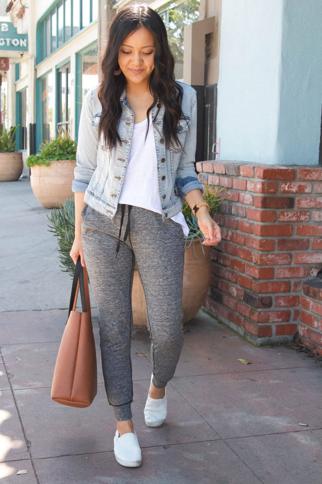 Casual Joggers Outfit: white tee + denim jacket + grey joggers + white slip-on sneakers + cognac tote