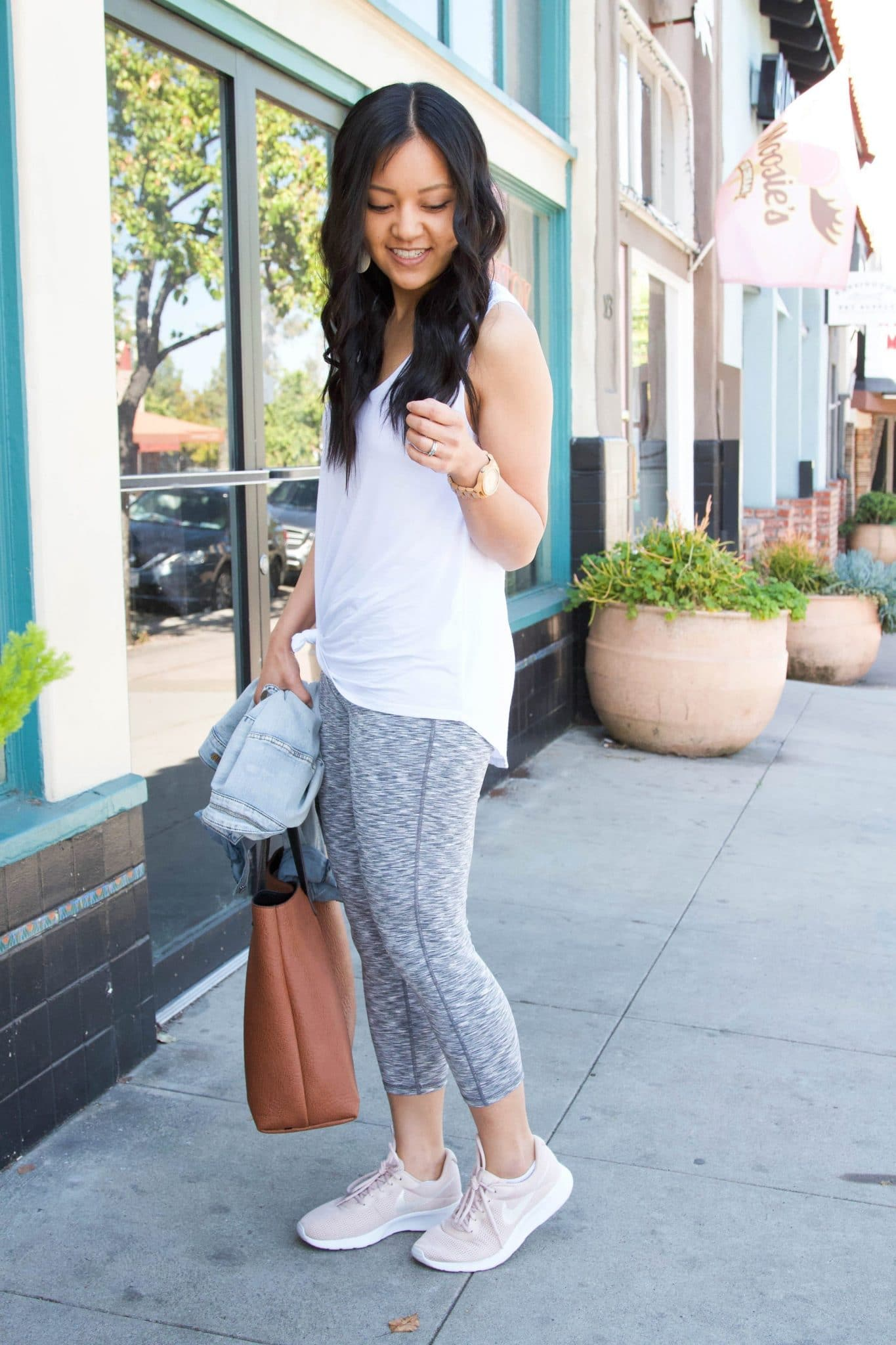 Casual Athleisure Outfit: white tank top + grey cropped leggings + denim jacket + blush sneakers + cognac tote