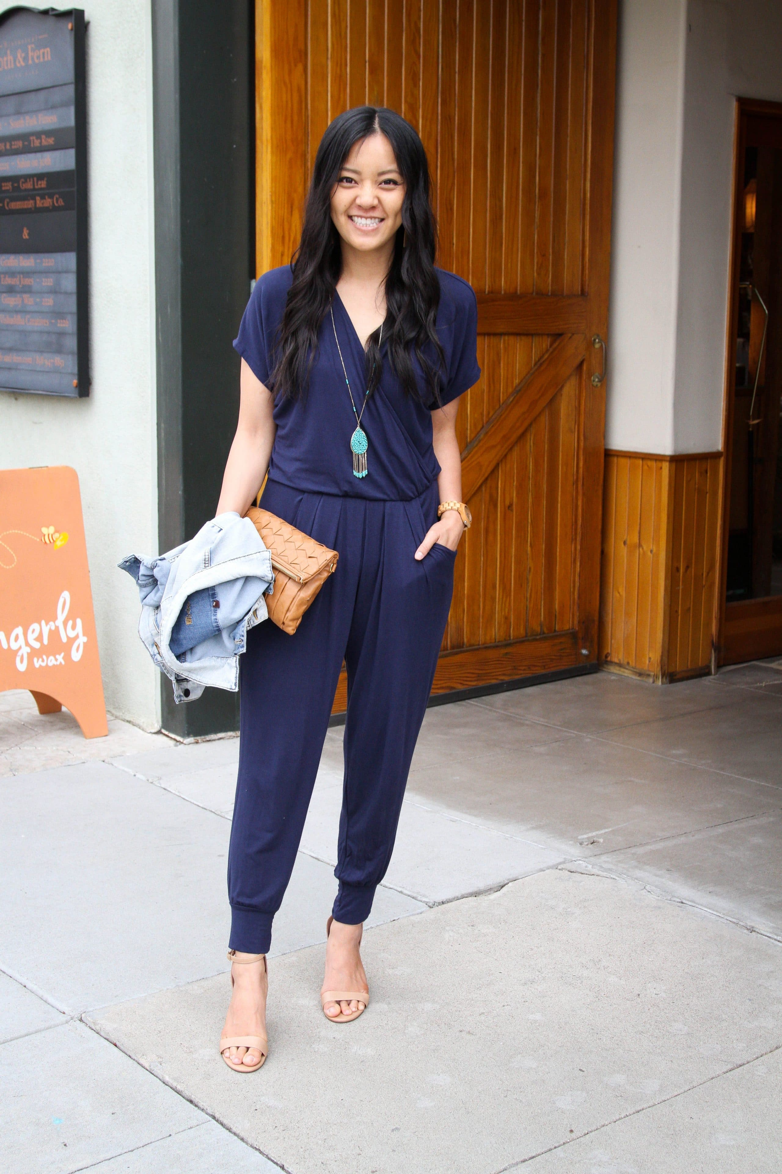 navy jumpsuit + denim jacket + colored pendant necklace + nude heels