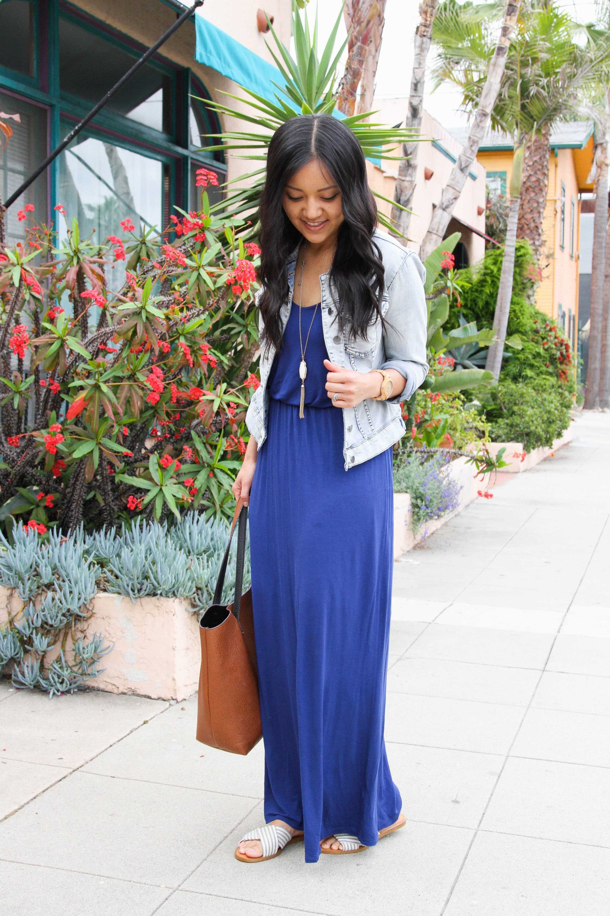 88b7c48f3 blue maxi dress, denim jacket, brown tote and pendant necklace looking down  whole body