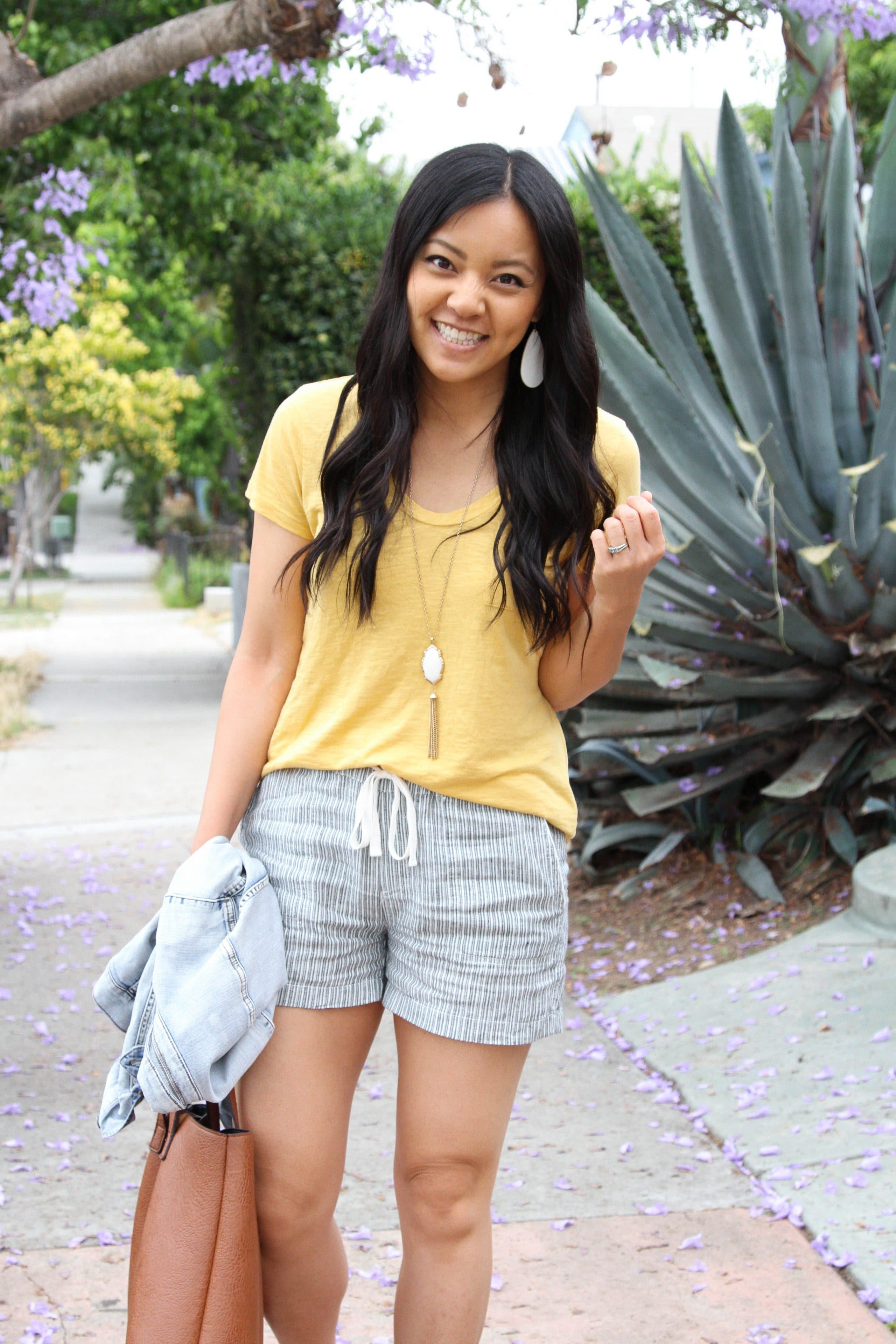 Blue linen shorts + yellow tee + White earrings + Denim jacket + tote bag