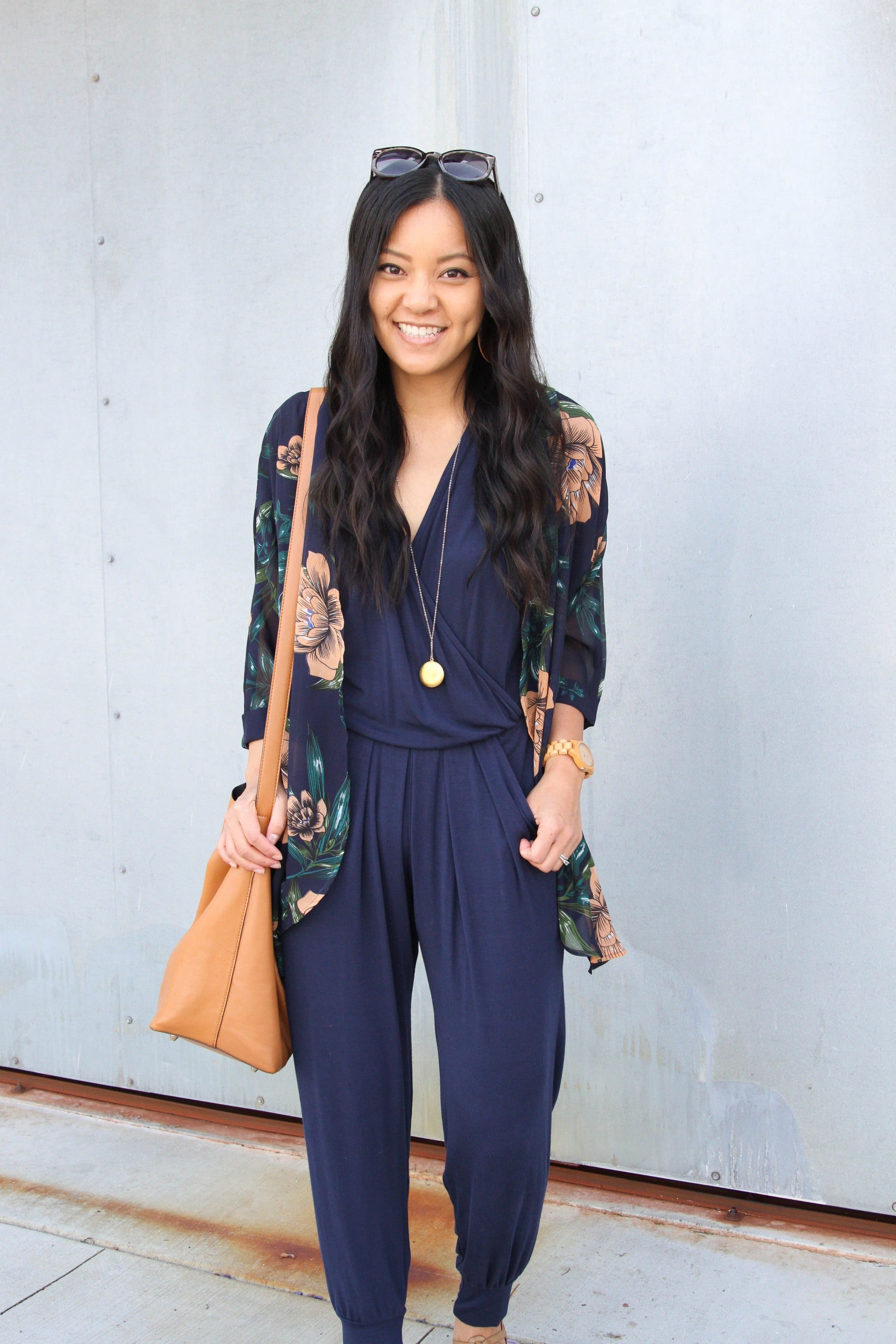 navy jumpsuit + floral wrap + cognac tote + pendant necklace