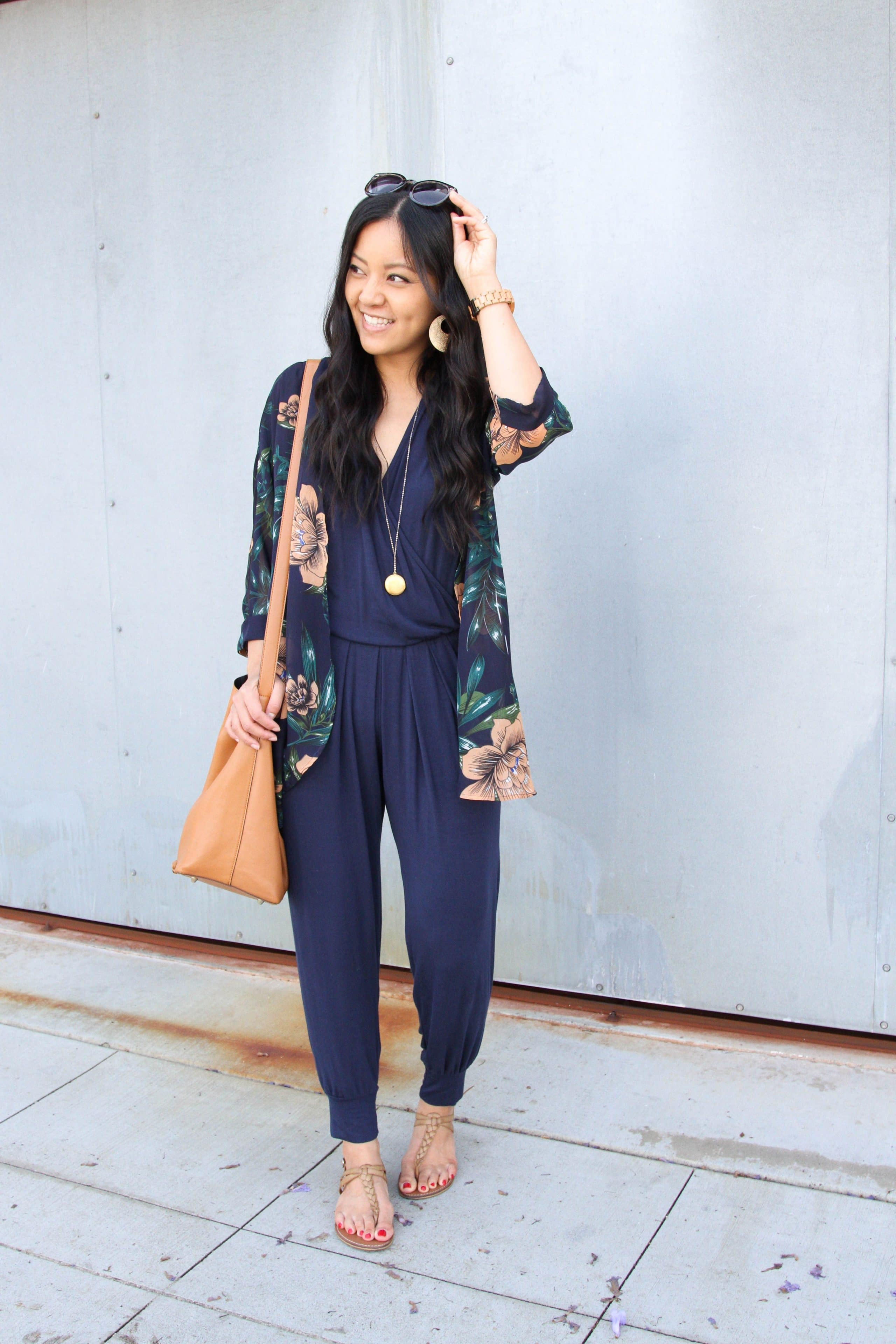 floral wrap + navy jumpsuit + tan sandals + long pendant necklace
