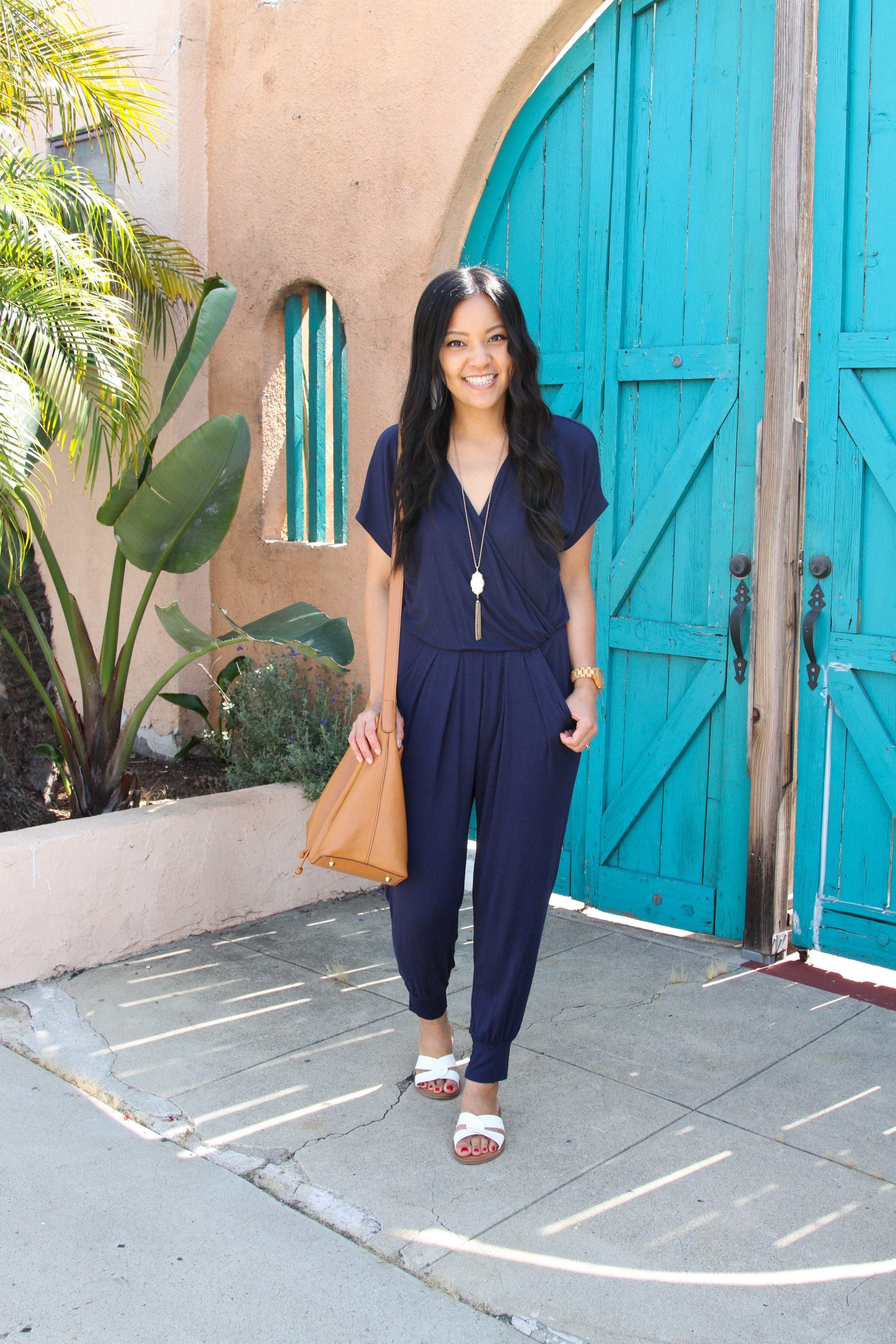 Navy jumpsuit + white sandals + cognac tote + pendant necklace