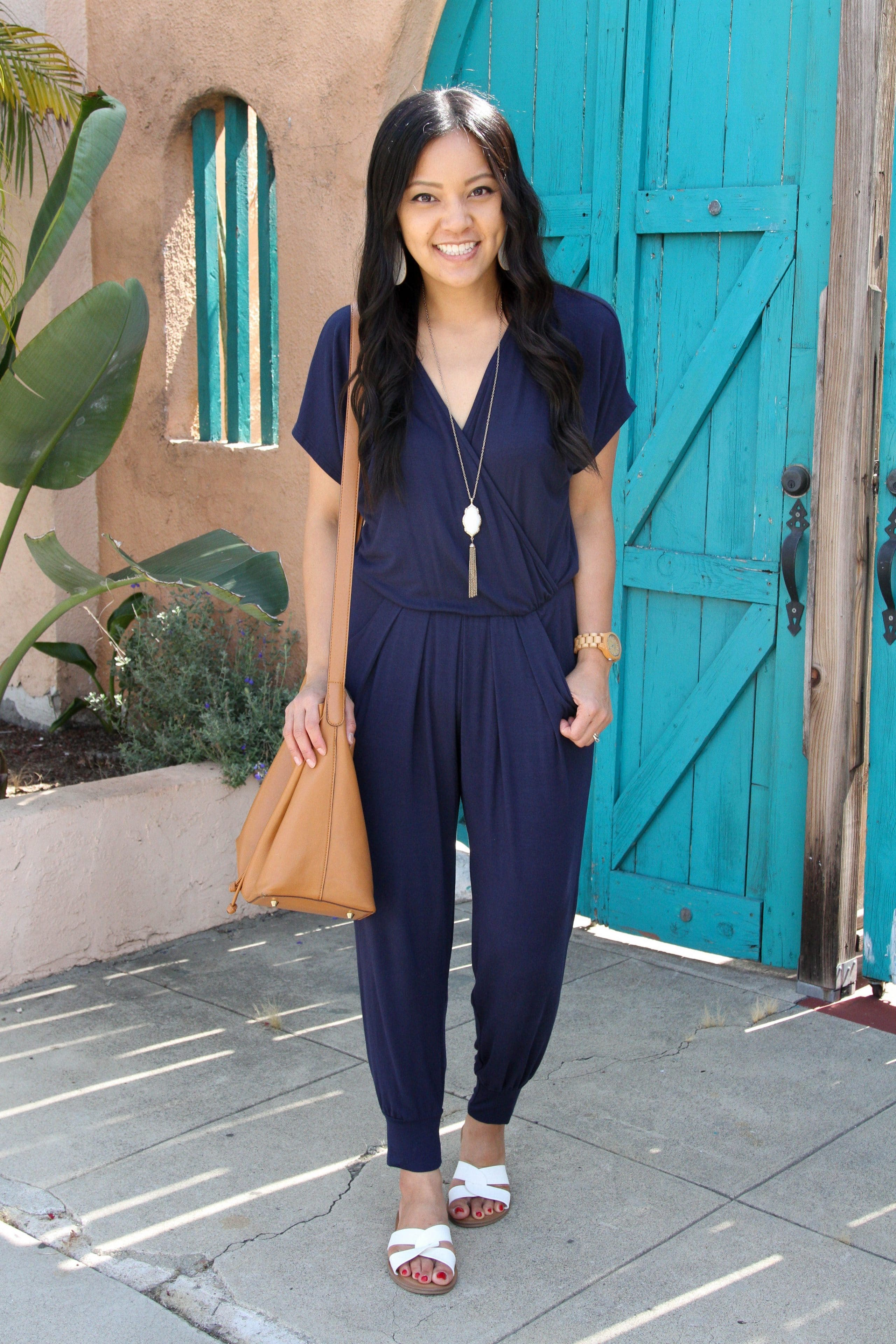 navy jumpsuit + cognac tote + long pendant necklace + white sandals