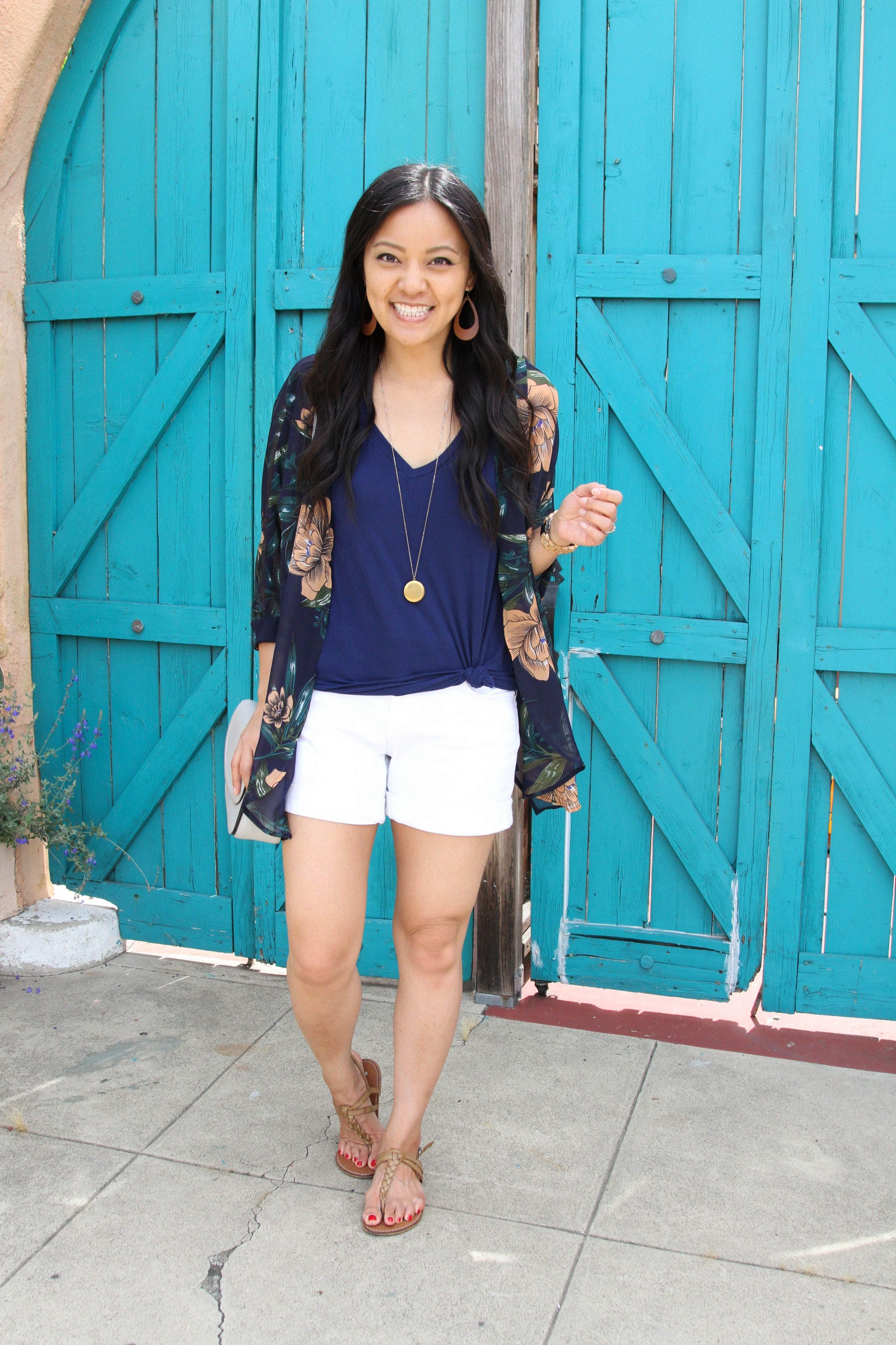 navy top + navy floral wrap + white shorts + tan sandals + long pendant necklace