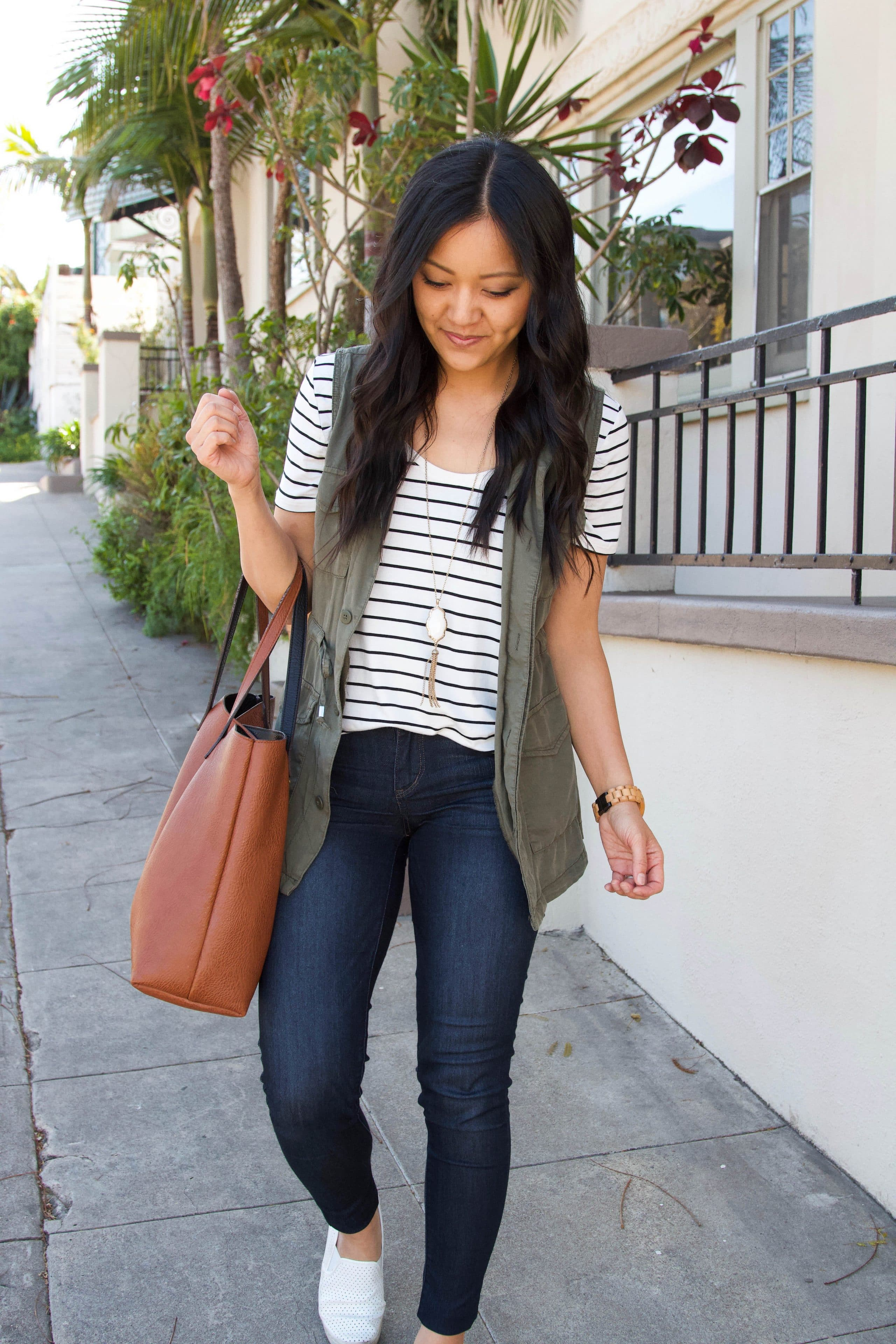 black and white striped tee + olive utility vest + denim skinny jeans + white loafers + cognac tote