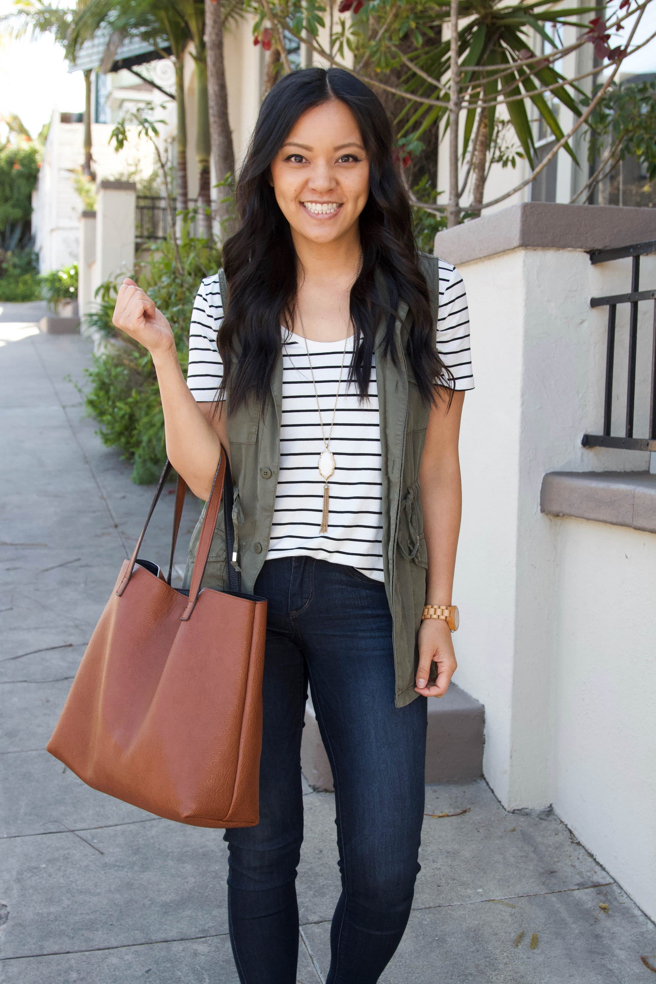 black and white striped tee + olive utility vest + denim skinny jeans + cognac tote