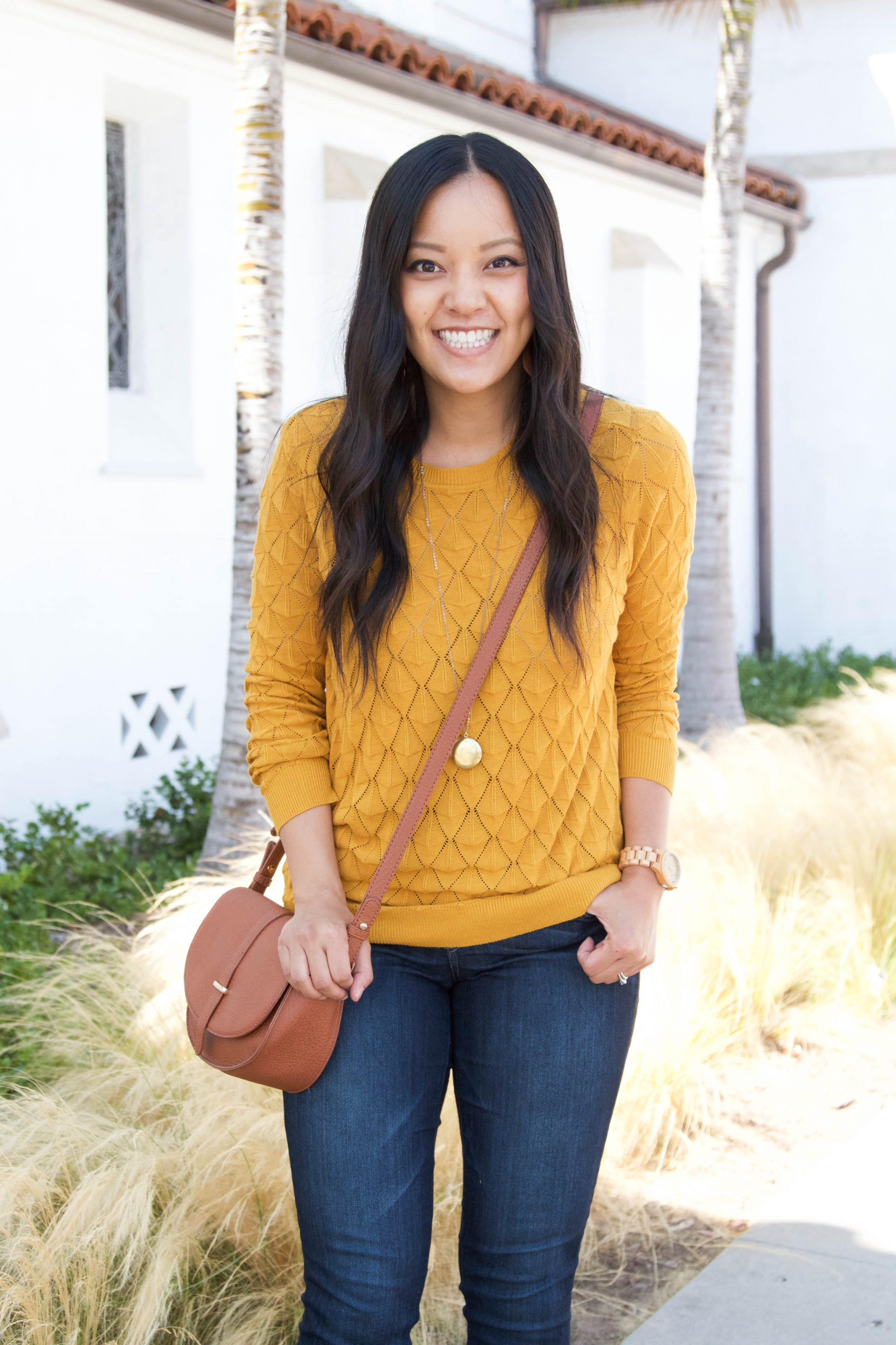 yellow sweater + bootcut jeans + taupe purse + long pendant necklace