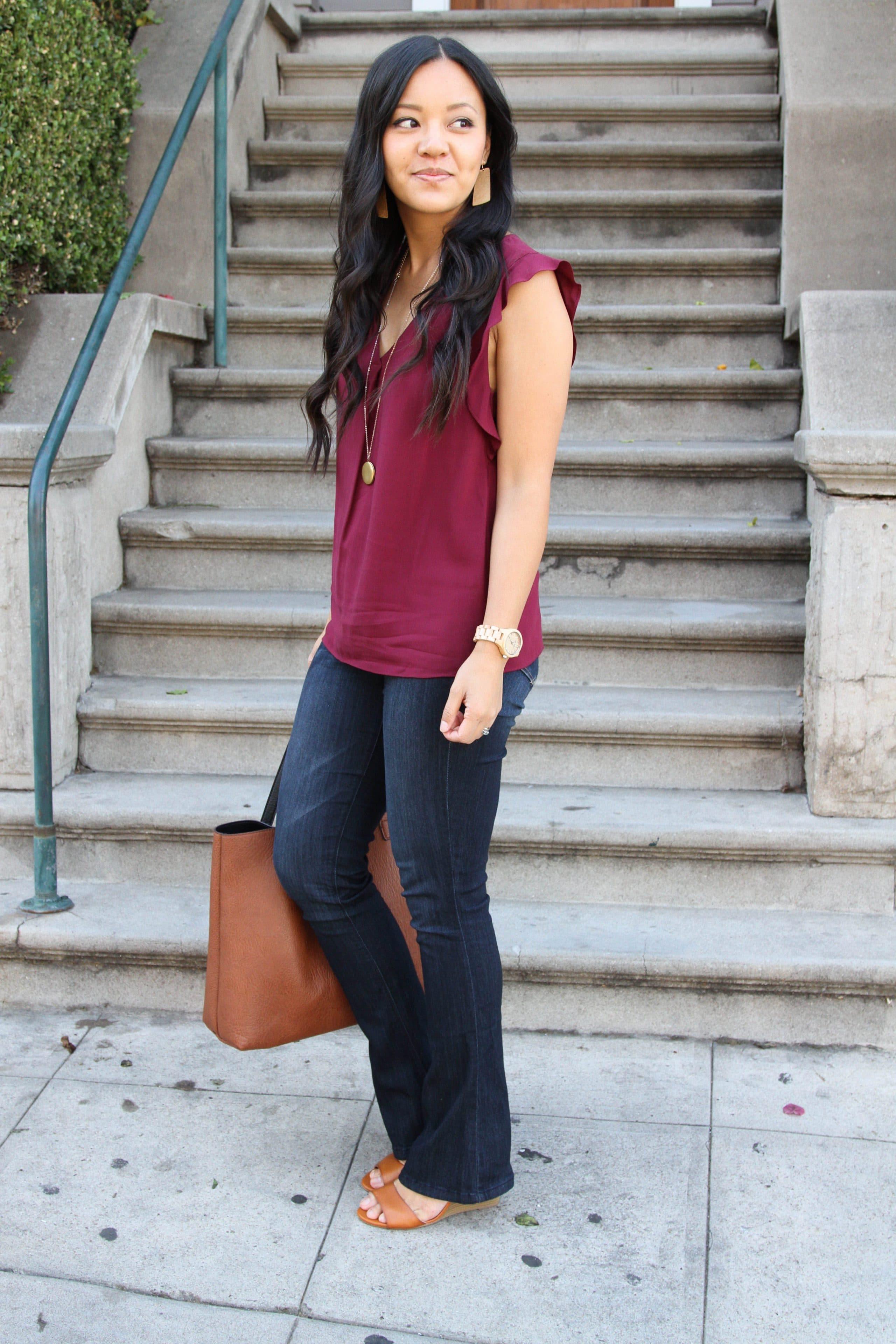 bootcut jeans + maroon top + wedges + cognac tote
