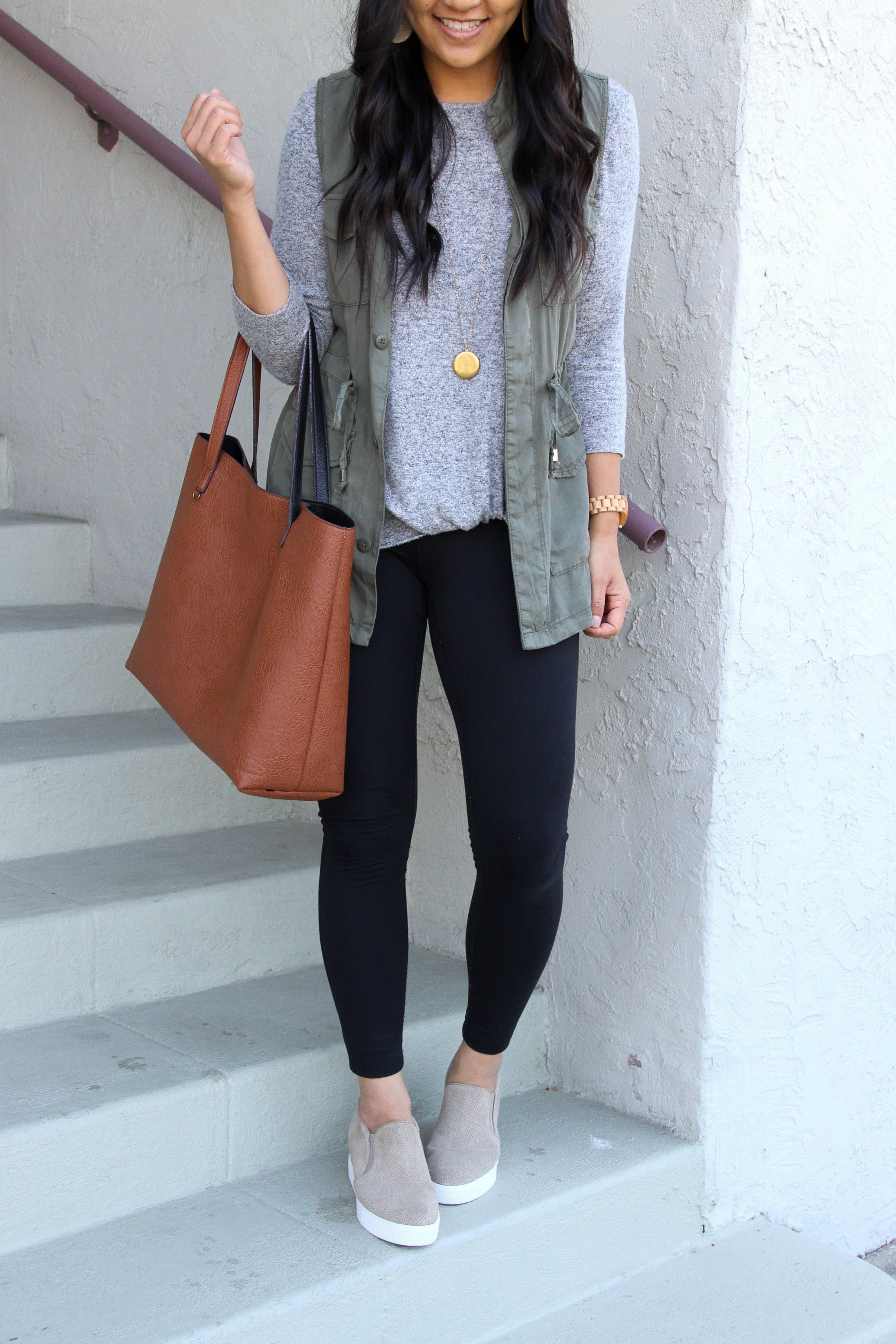 grey twist top + black leggings + olive utility vest + brown tote + taupe sneakers + pendant necklace