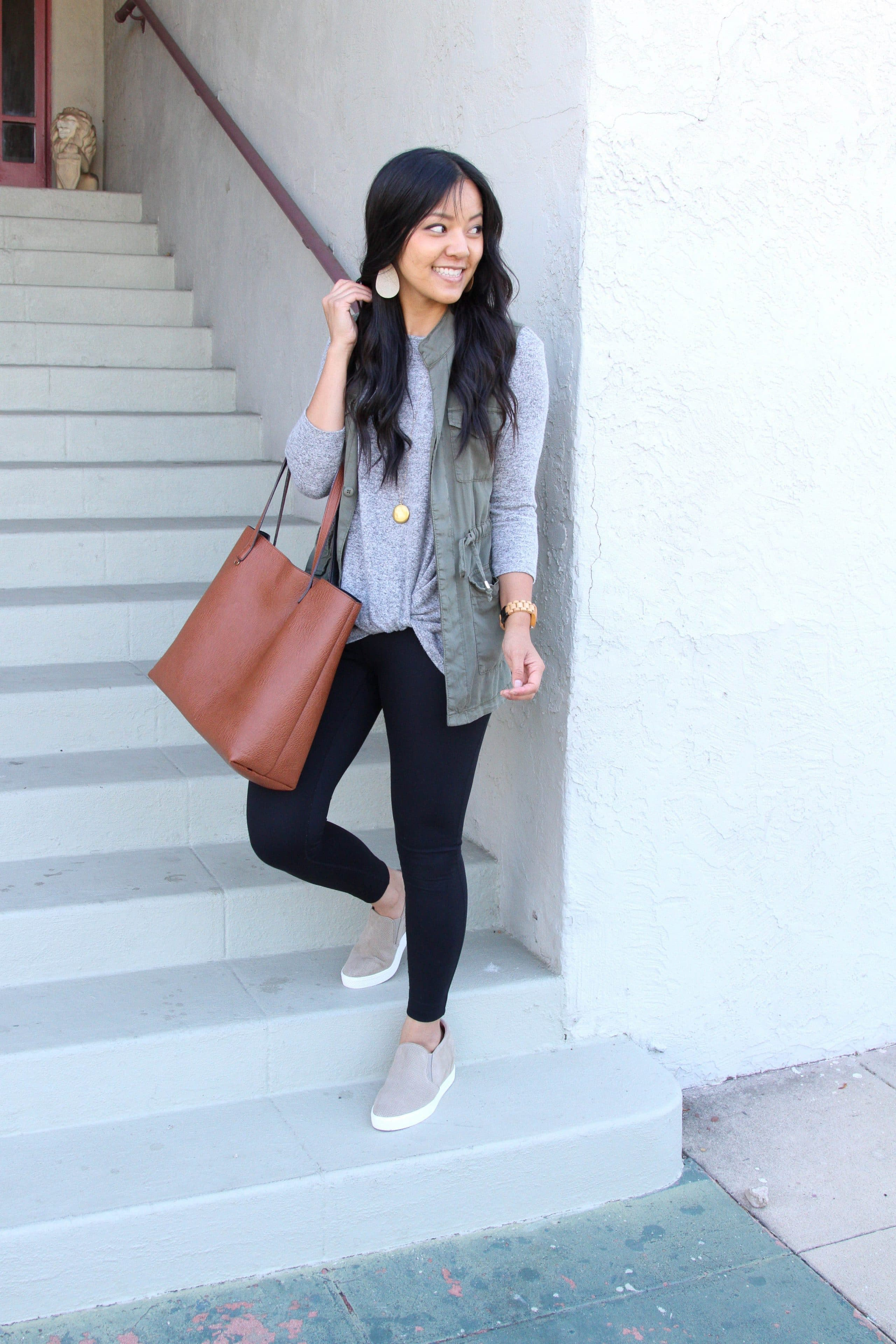 olive utility vest + grey twist top + black leggings + taupe sneakers + brown tote