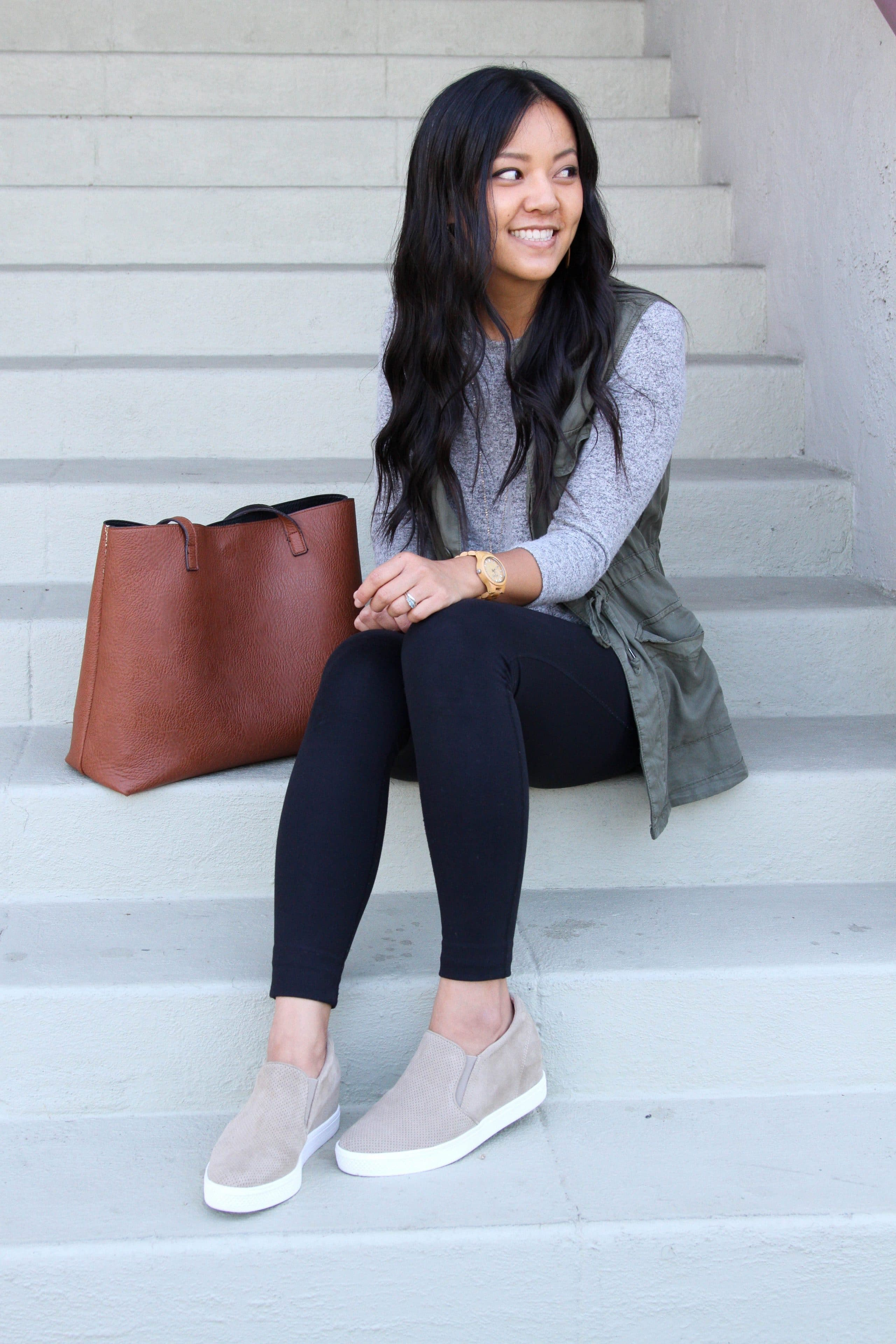 black leggings + taupe sneakers + utility vest + grey twist top + brown tote