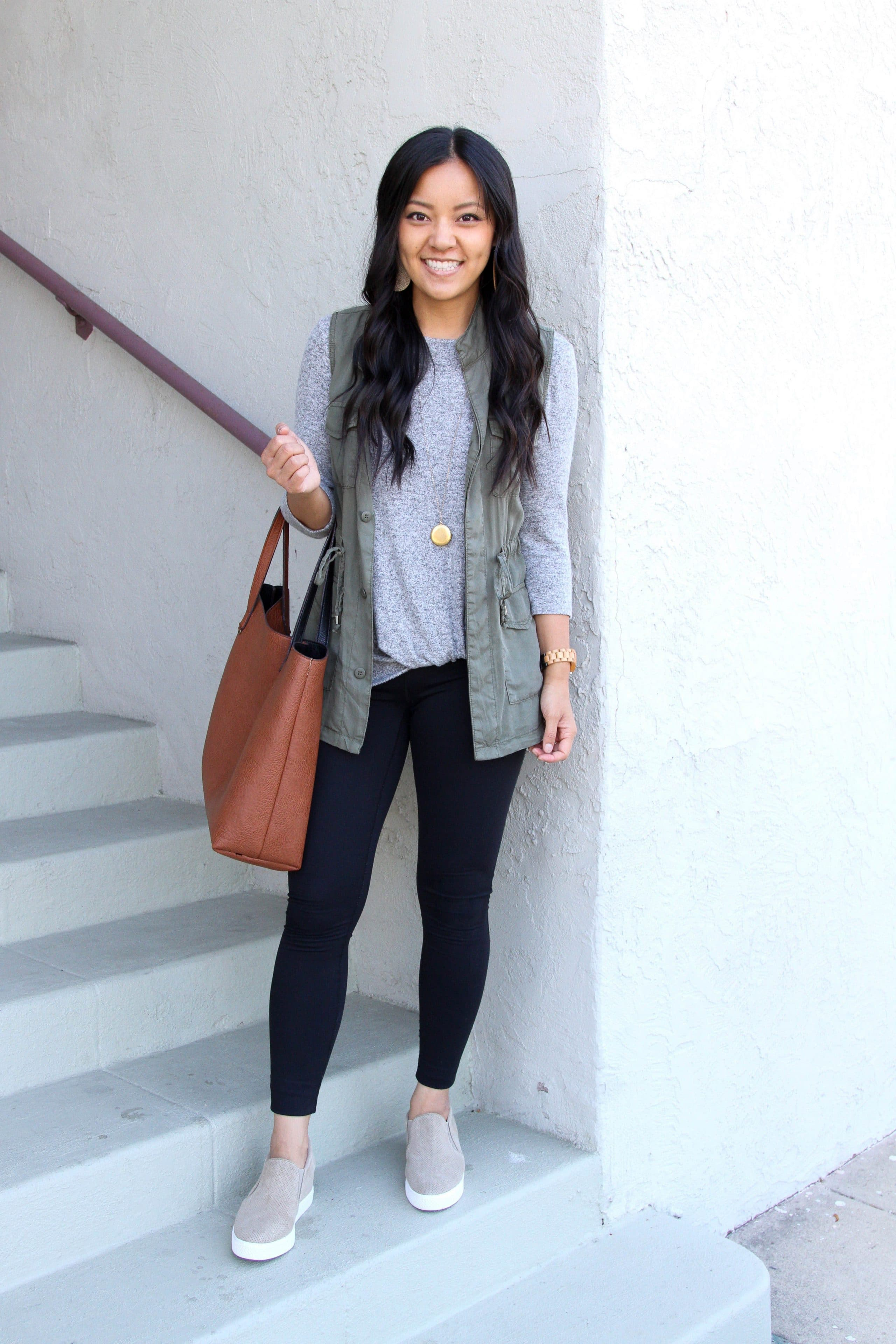 grey twist shirt + olive utility vest + black leggings + taupe sneakers + cognac tote + pendant necklace
