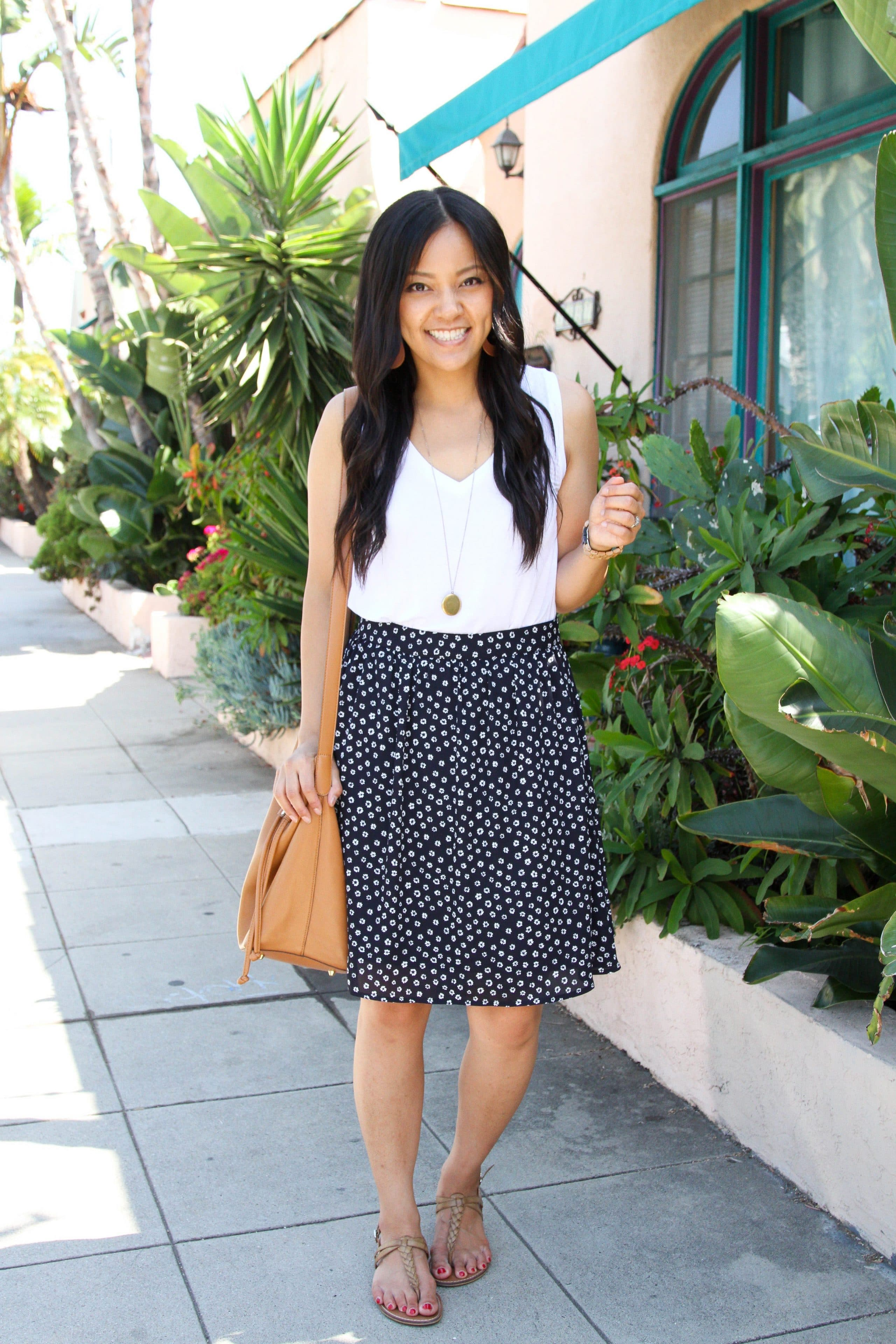 white tank top + black floral skirt + tan sandals + long pendant necklace + tan purse