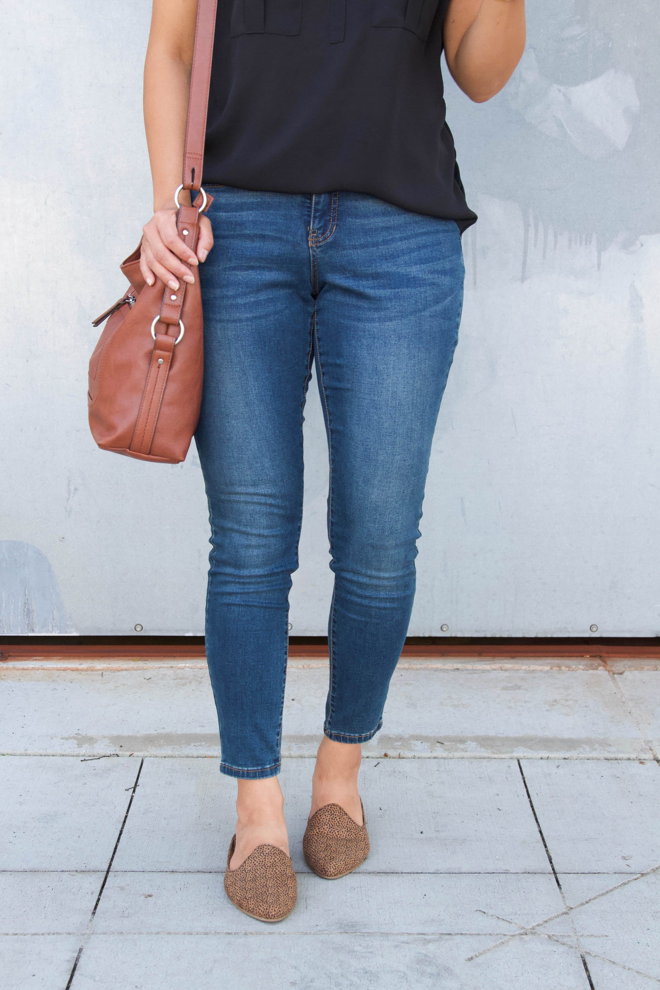 black top + skinny jeans + leopard mules + cognac purse