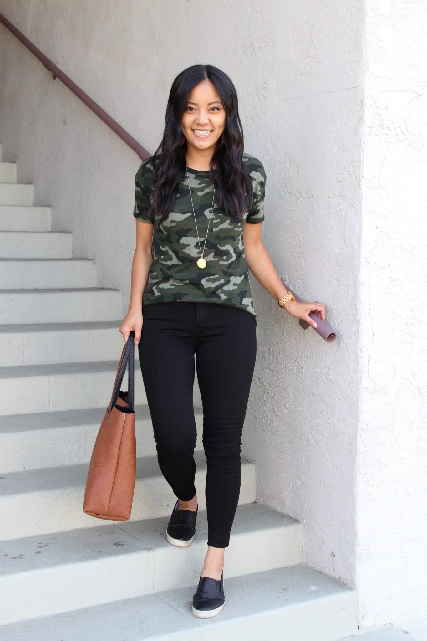 Casual Fall Outfit: camo tee + black skinny jeans + black slip-on sneakers + cognac tote + gold circle pendant necklace
