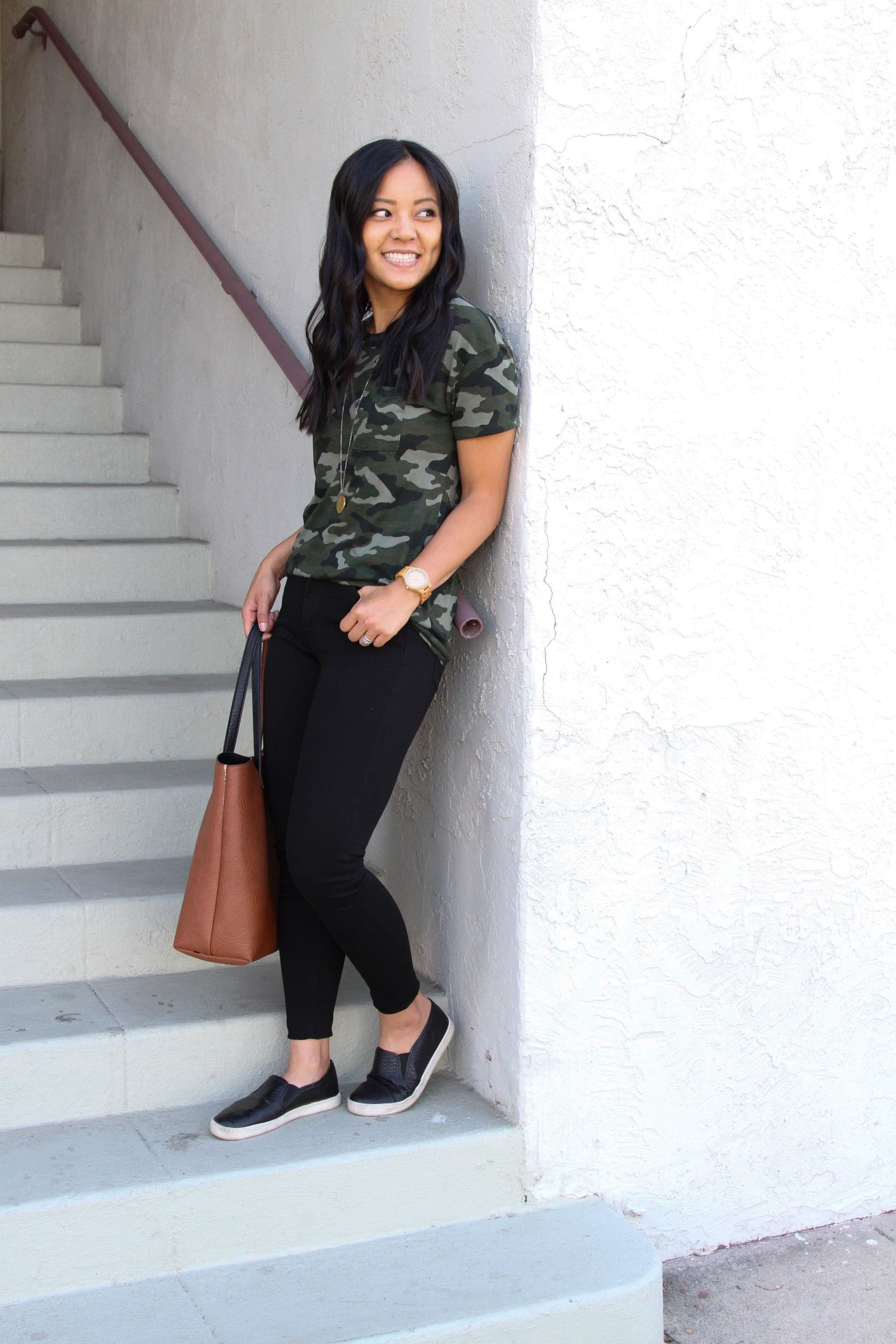 black skinny pants + green camo shirt + black slip on shoes + cognac tote