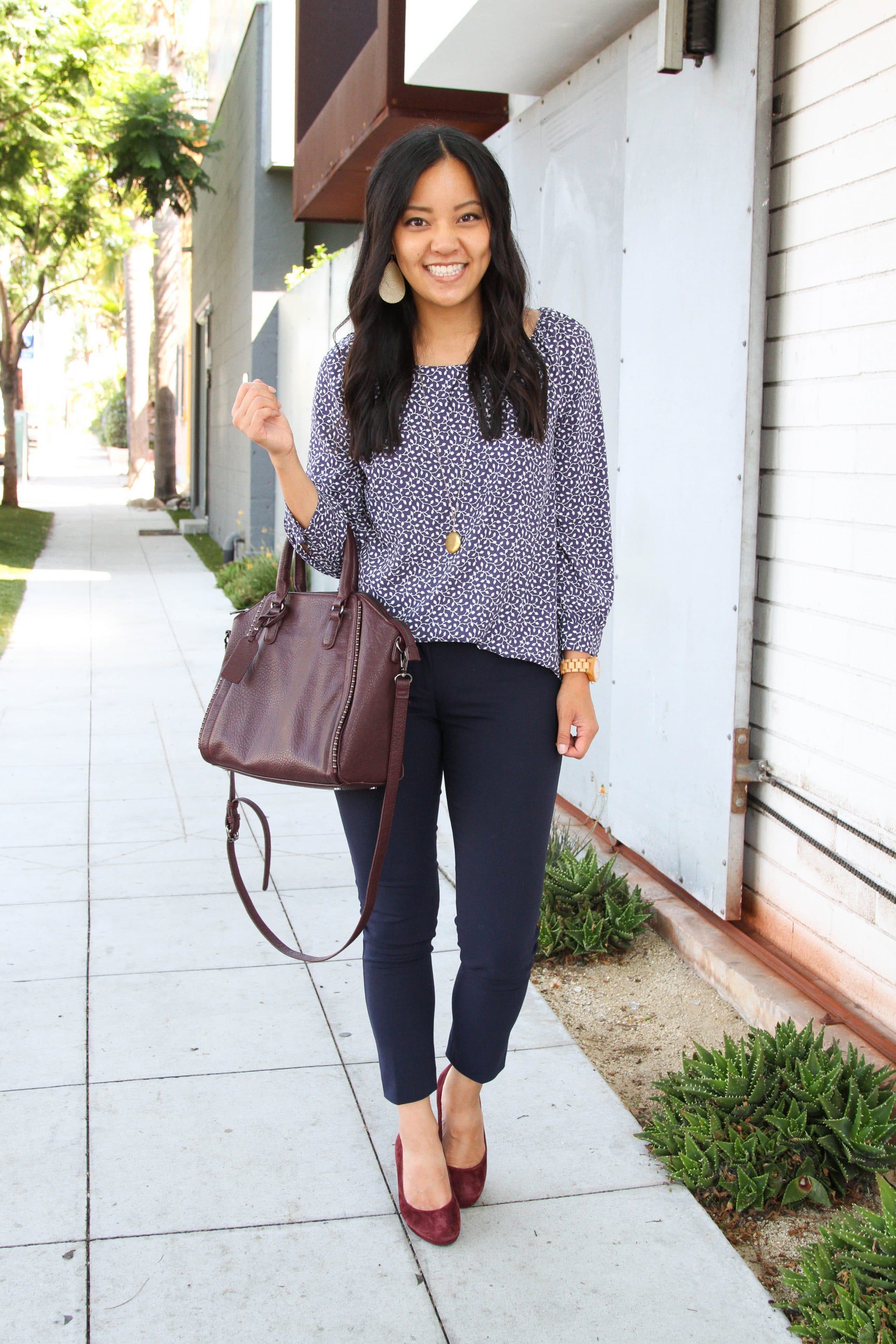 business casual + navy and white floral top + navy pants + maroon pumps + maroon purse