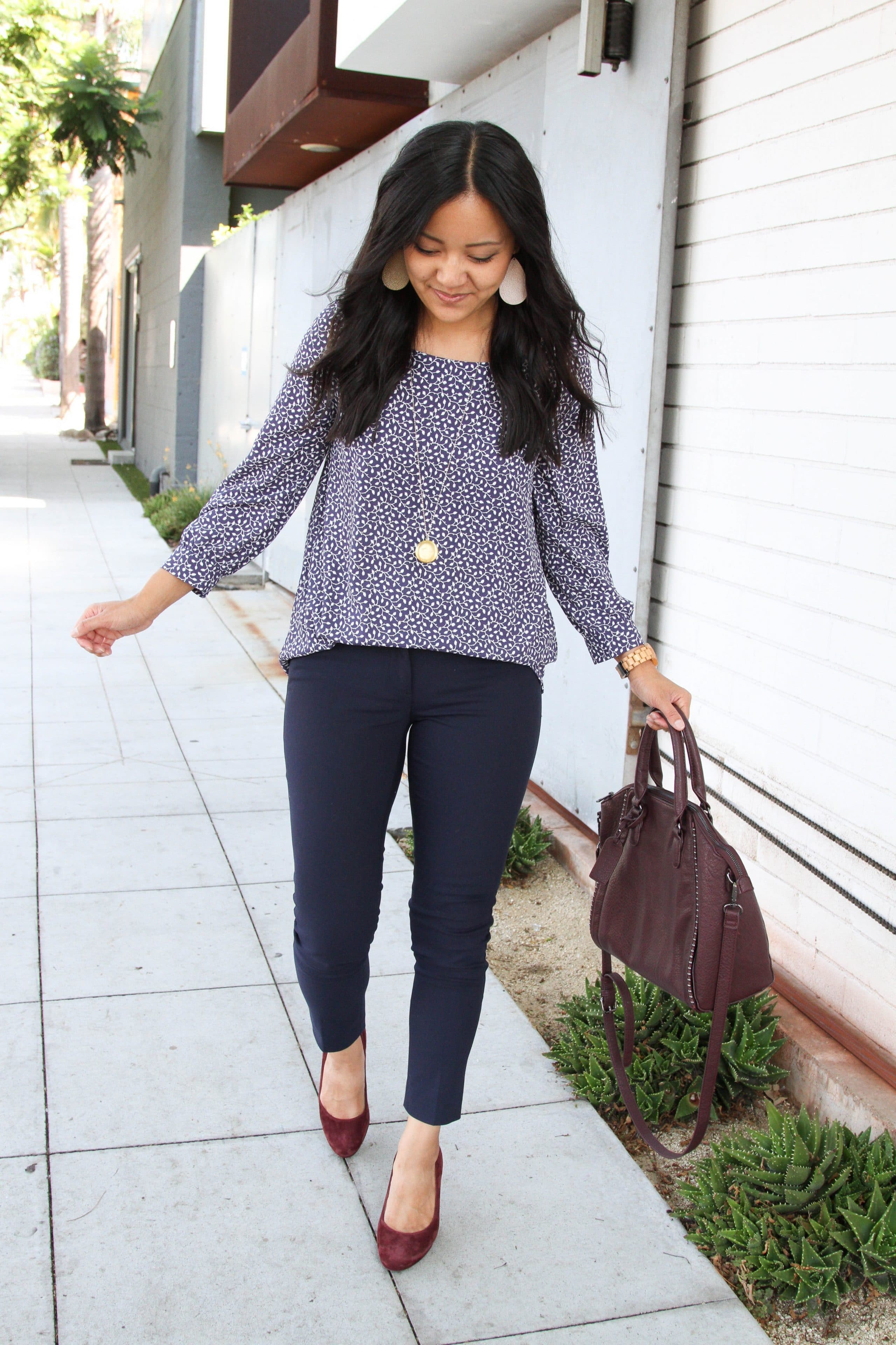 business casual + navy pants + navy and white floral top + maroon pumps + maroon purse