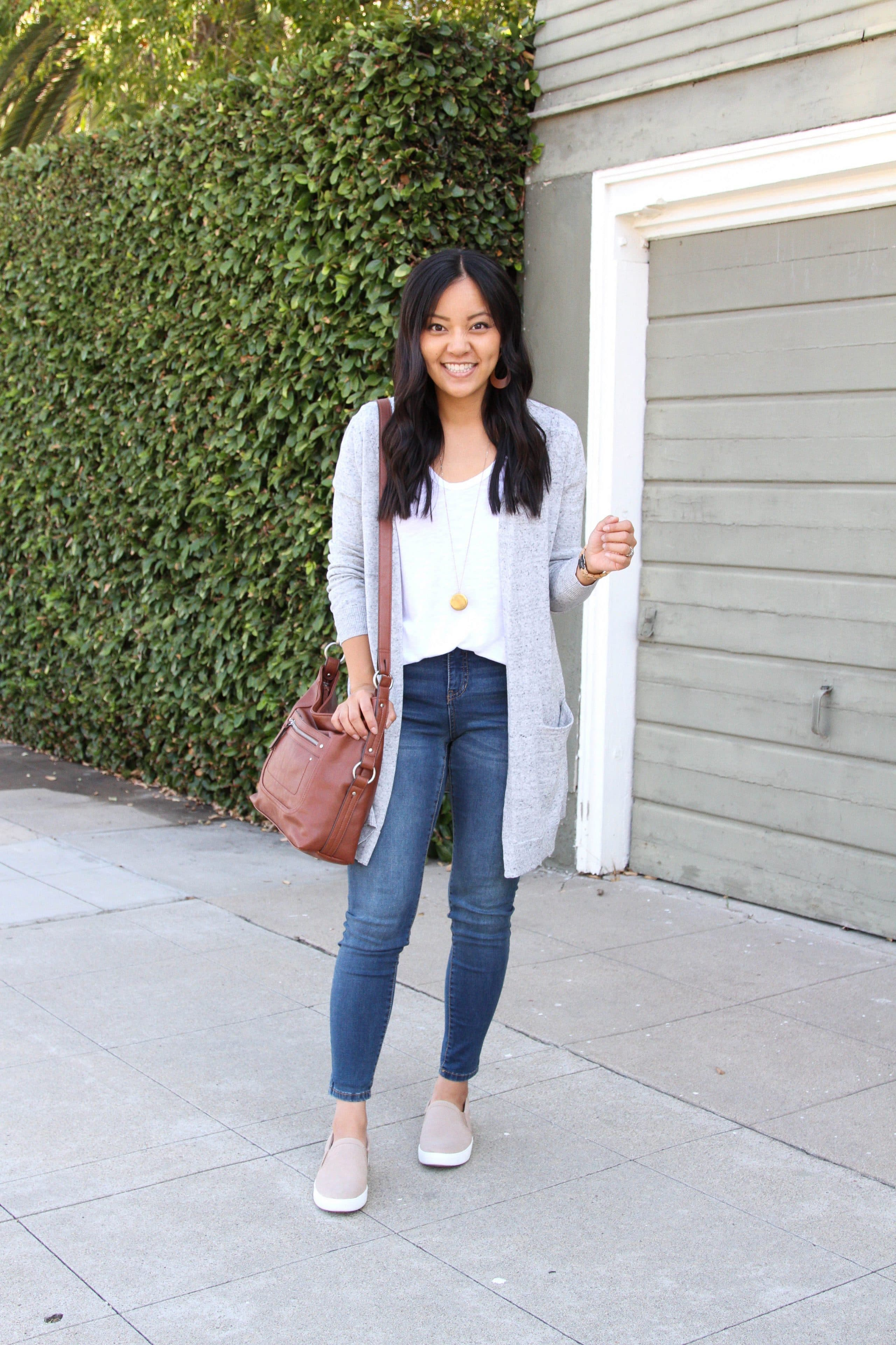 white tee + grey sweater + skinny jeans + tan slip on sneakers + cognac purse