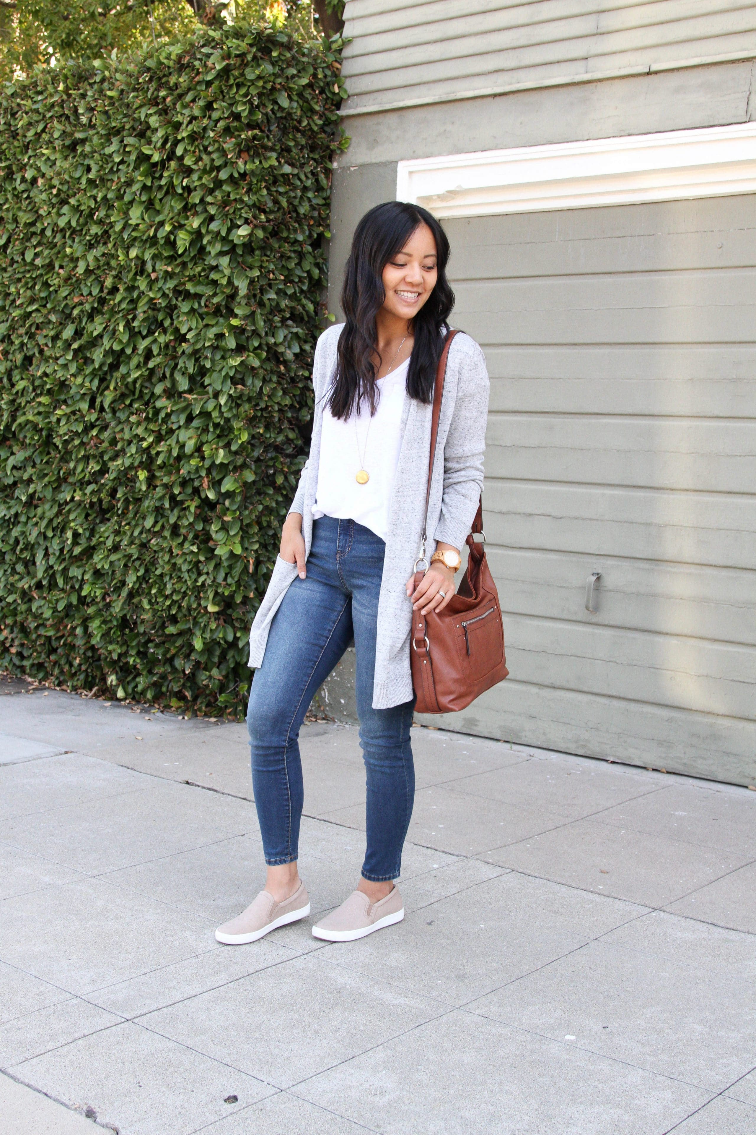 white tee + grey sweater + cognac purse + skinny jeans + tan slip on sneakers