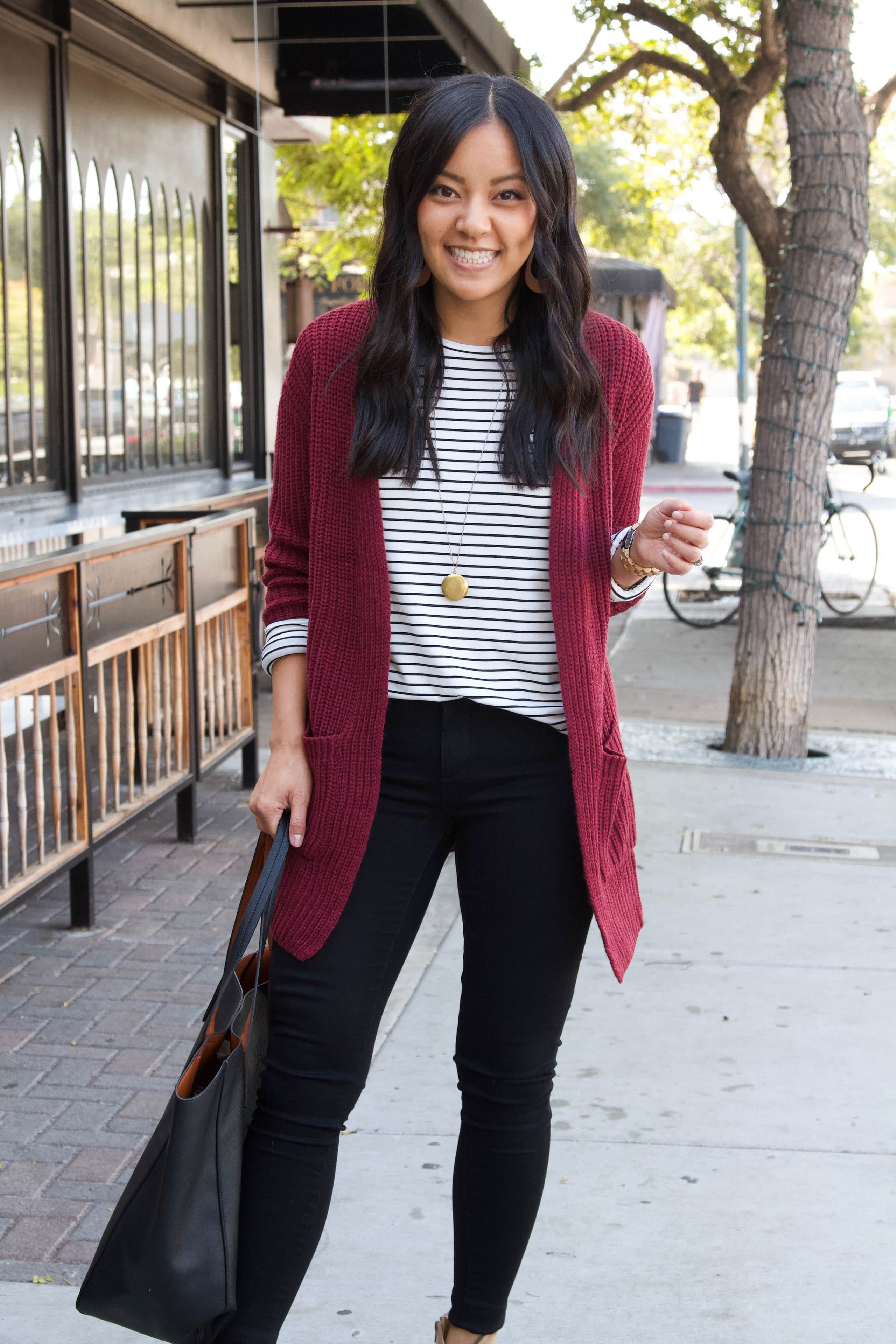black and white striped shirt + maroon cardigan + taupe booties + black skinny pants + black tote + business casual outfit