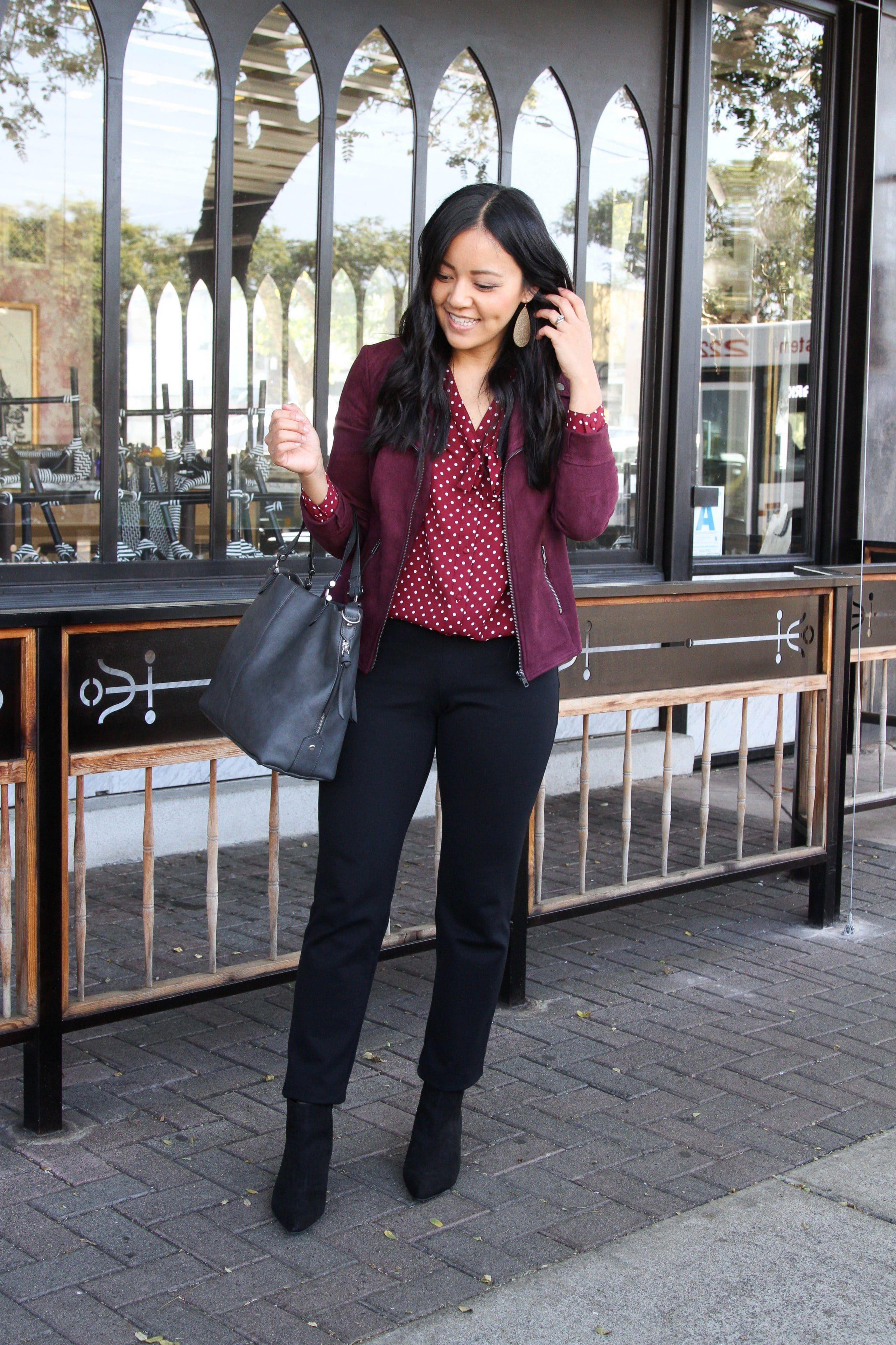 business casual + maroon moto jacket + maroon polka dot top + black straight pants + black booties + grey purse