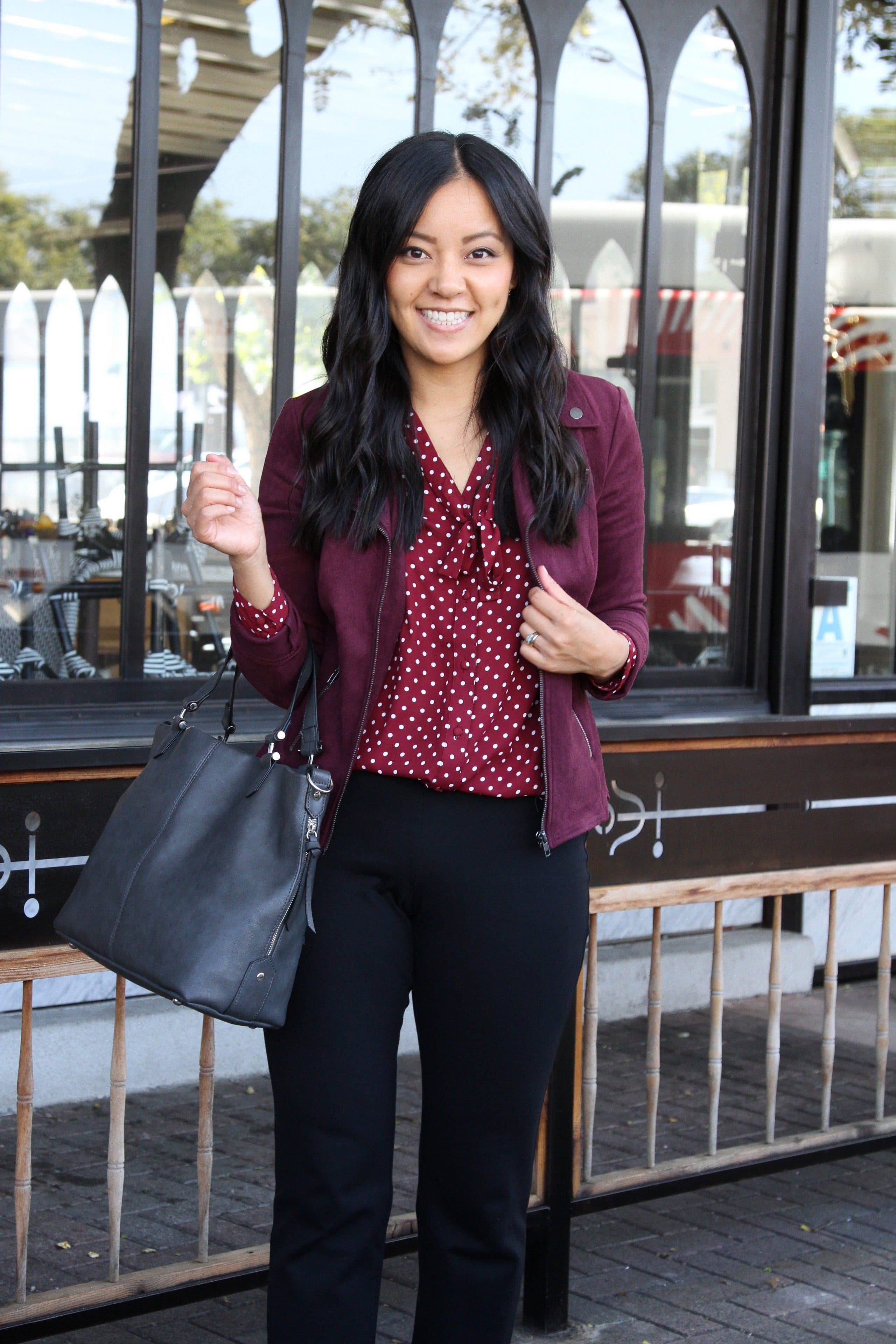 maroon polka dot top + maroon moto jacket + black straight pants + black booties + grey purse + business casual outfit