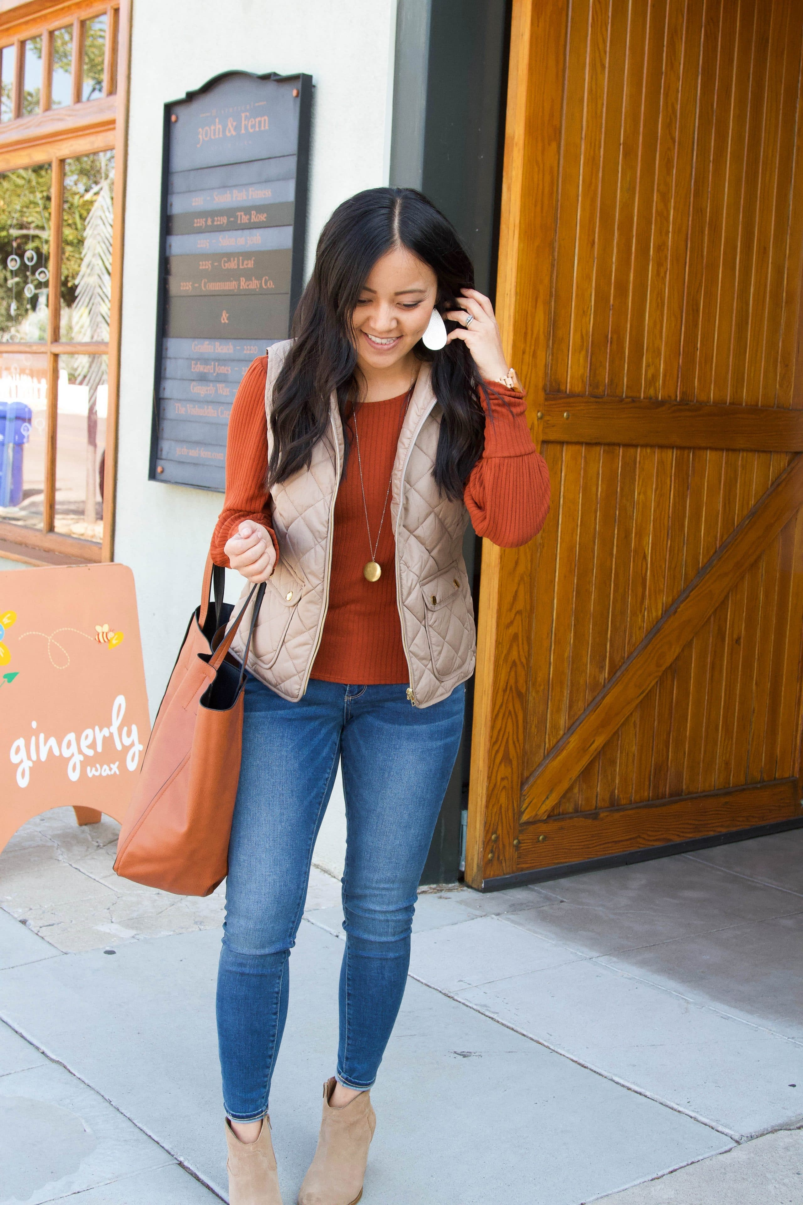rust orange sweater + tan vest + skinny jeans + taupe booties + cognac tote