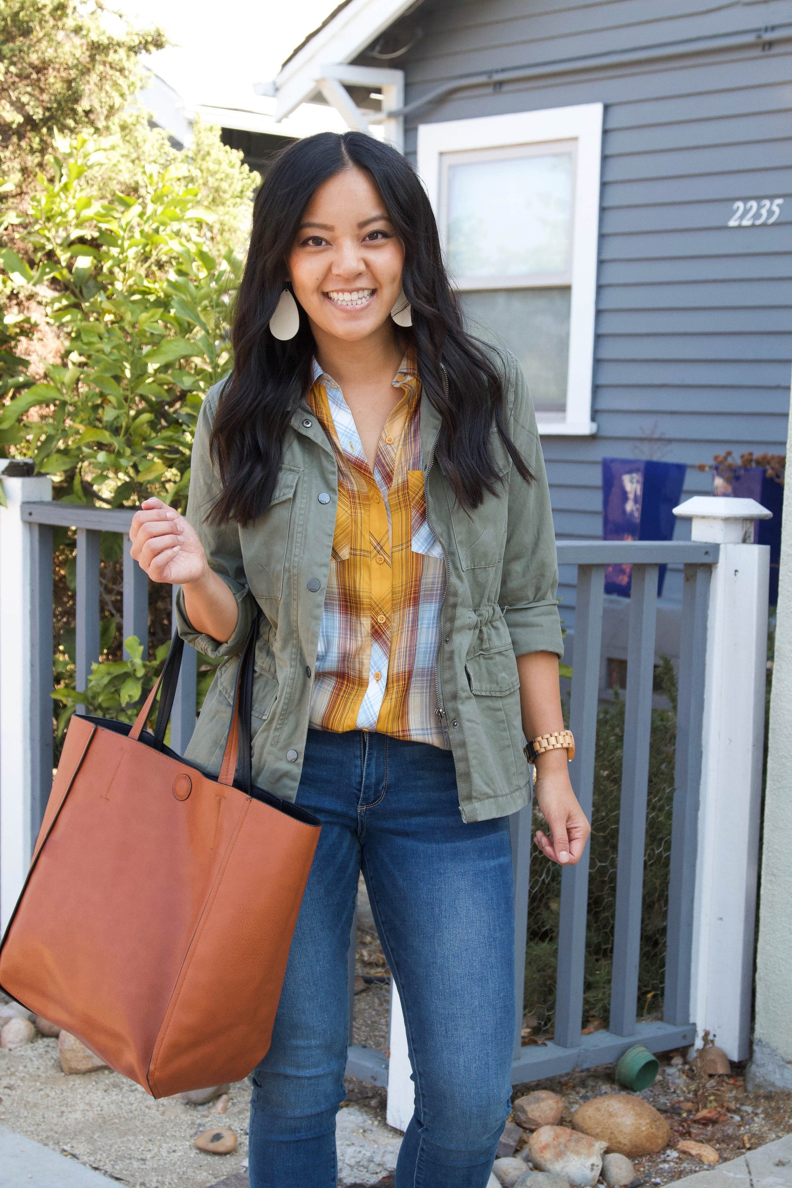 olive utility jacket + yellow plaid top + skinny jeans + taupe booties + cognac tote