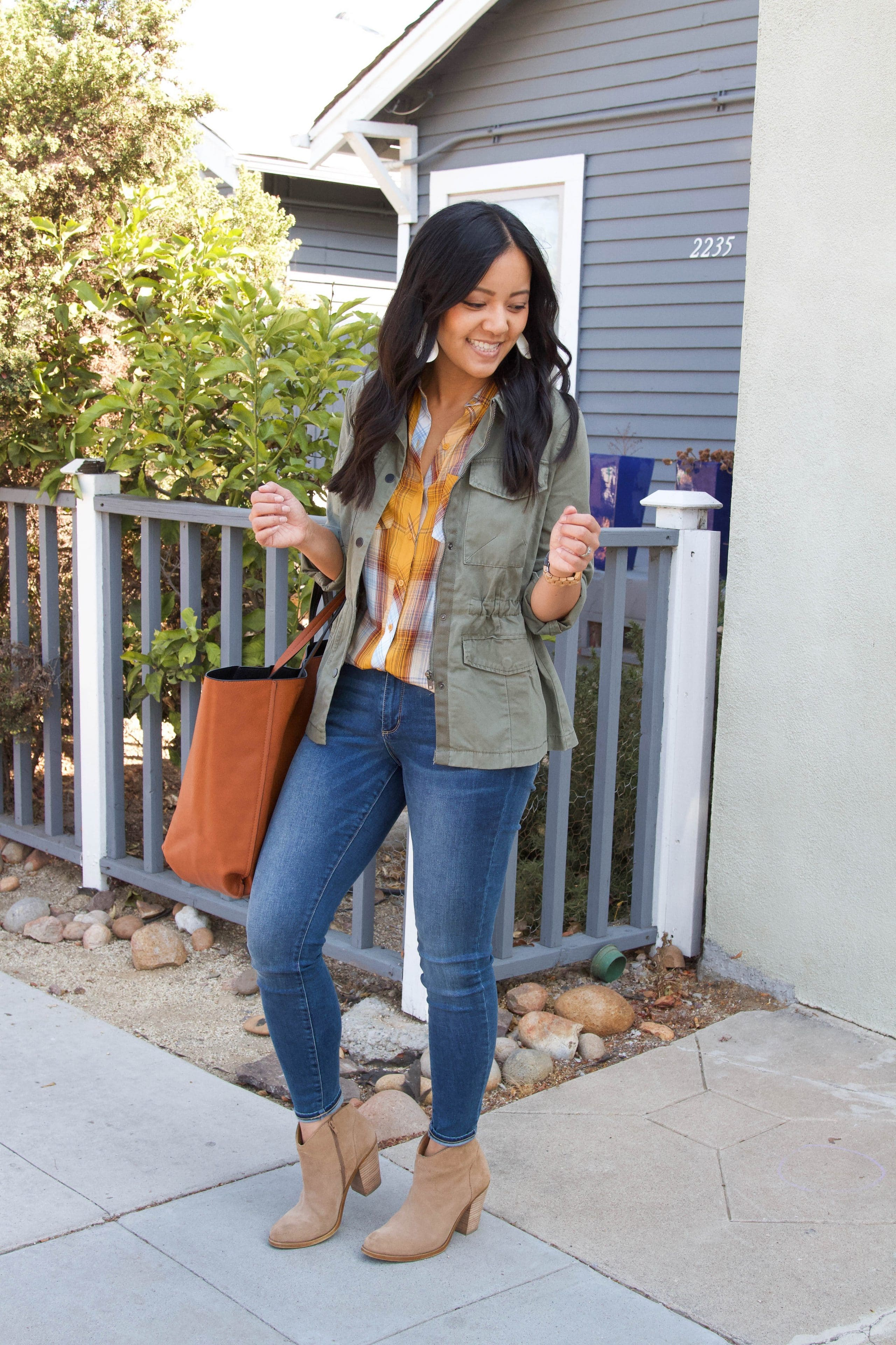 yellow plaid top + skinny jeans + olive utility jacket + taupe booties + cognac tote